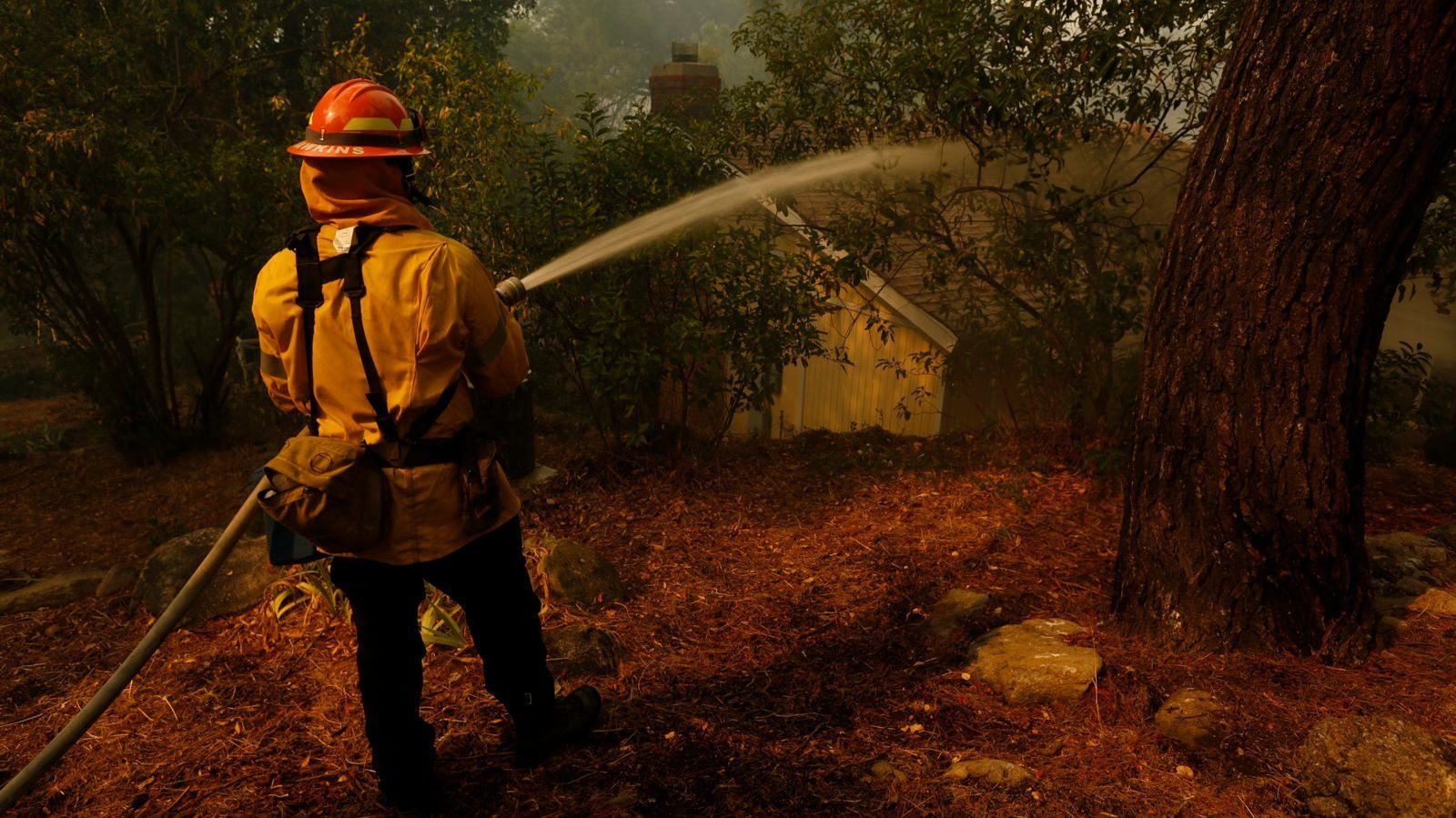 Los Angeles City firefighter Robert Hawkins hoses down a home to protect it from the La Tuna fire in Sunland.