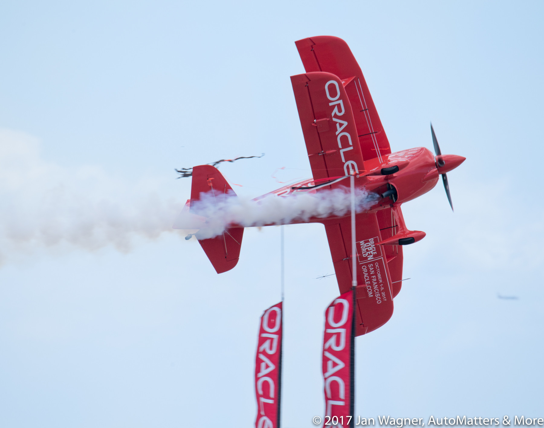 Sean Tucker flying his Oracle Challenger III aerobatic biplane through a ribbon suspended between two banners