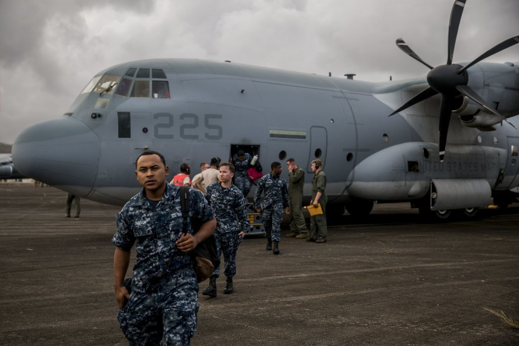 In this U.S. Navy handout, U.S. Marines and sailors assigned to the 26th Marine Expeditionary Unit (26th MEU) exit a KC-130J Super Hercules aircraft attached to Marine Aerial Refueler Transport Squadron (VMGR) 252 at Jose Aponte de la Torre Airport in Puerto Rico, Sept. 27, 2017.