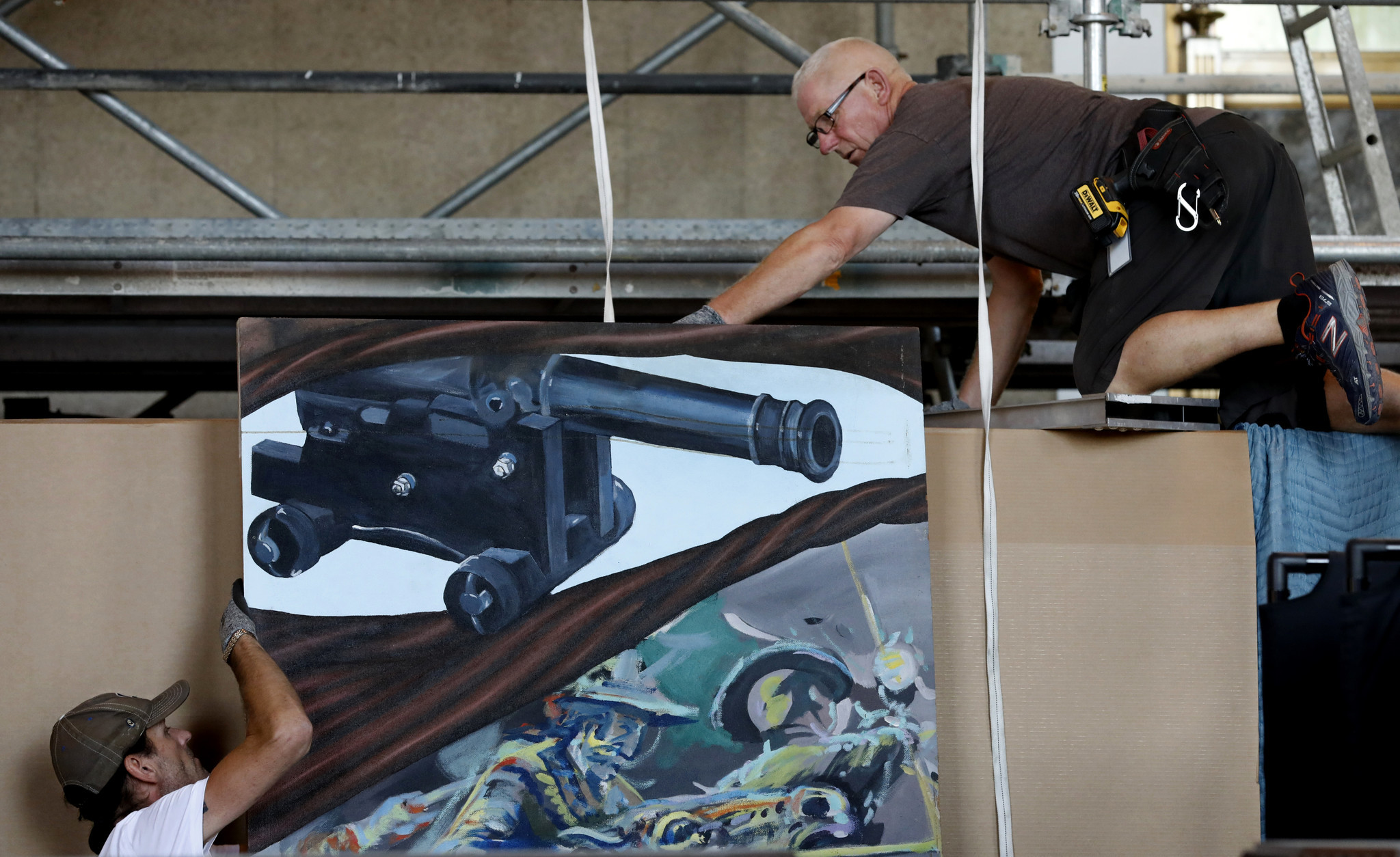 Kevan Overend, left, and Alan Bolger work on putting another panel into place. This one depicts a cannon used to defend the city in the Mexican American War.