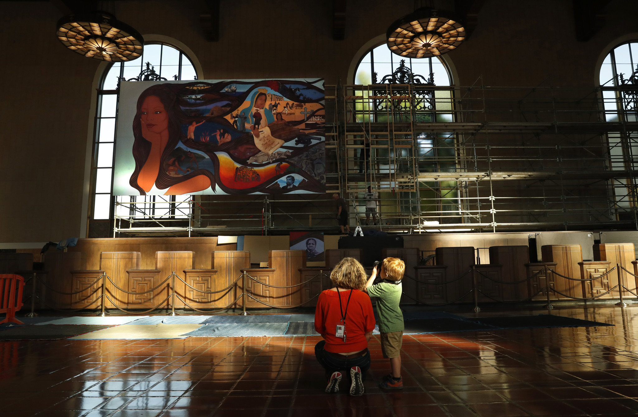 Co-curator Jessica Hough and her son Ansel, 4, pause to take in Barbara Carrasco's mural during its Union Station installation, which is now complete.