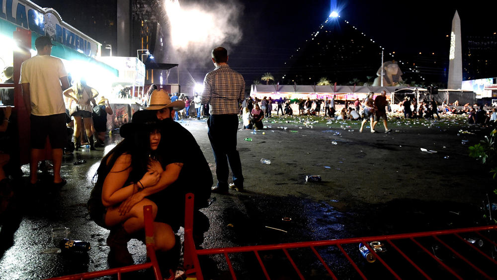 People take cover from the Route 91 Harvest country music festival after hearing gunfire Sunday night in Las Vegas. The shooter was firing from the nearby Mandalay Bay Resort and Casino. (Getty Images)