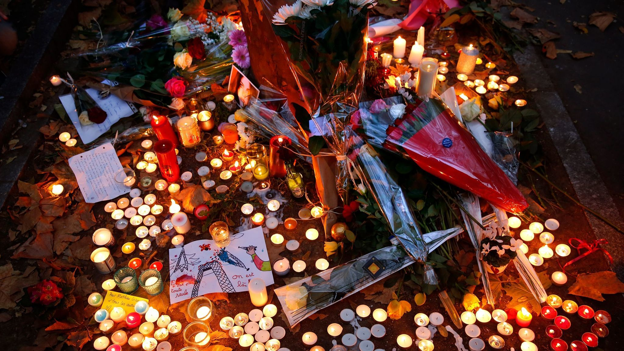 People pay tribute to those who died in the Nov. 13, 2015 Paris attacks at the Bataclan Theatre.