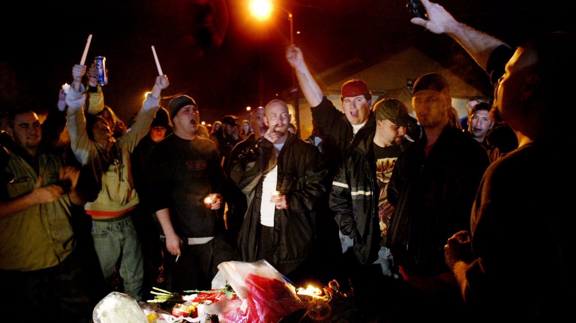 """Fans of """"Dimebag"""" Darrell Abbott sing during a candlelight vigil outside the Alrosa Villa club in Columbus, Ohio, on Dec. 9, 2004."""