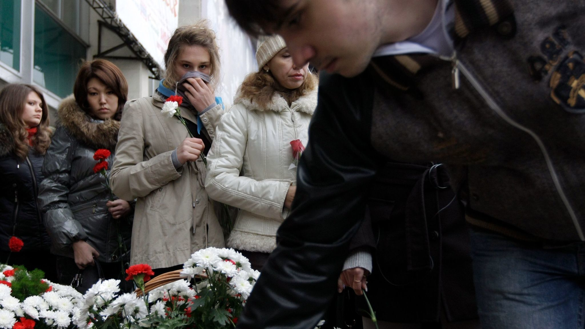 People lay flowers outside the Moscow theater that Chechen gunmen seized in 2002. Relatives of the slain hostages mark the tragedy's seventh anniversary Oct. 26, 2009.