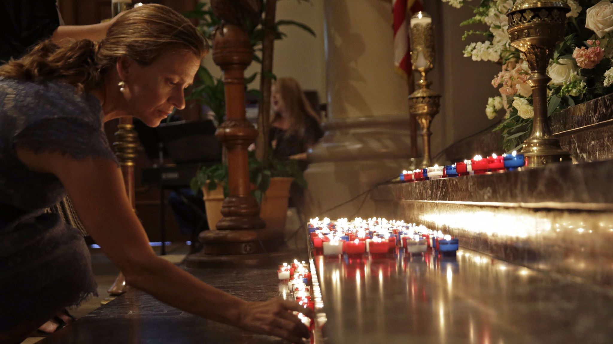 A woman places a candle on the altar during a prayer service for the victims of the Grand 16 theater shooting at the Cathedral of St. John the Evangelist, in Lafayette, La., on July 26, 2015.