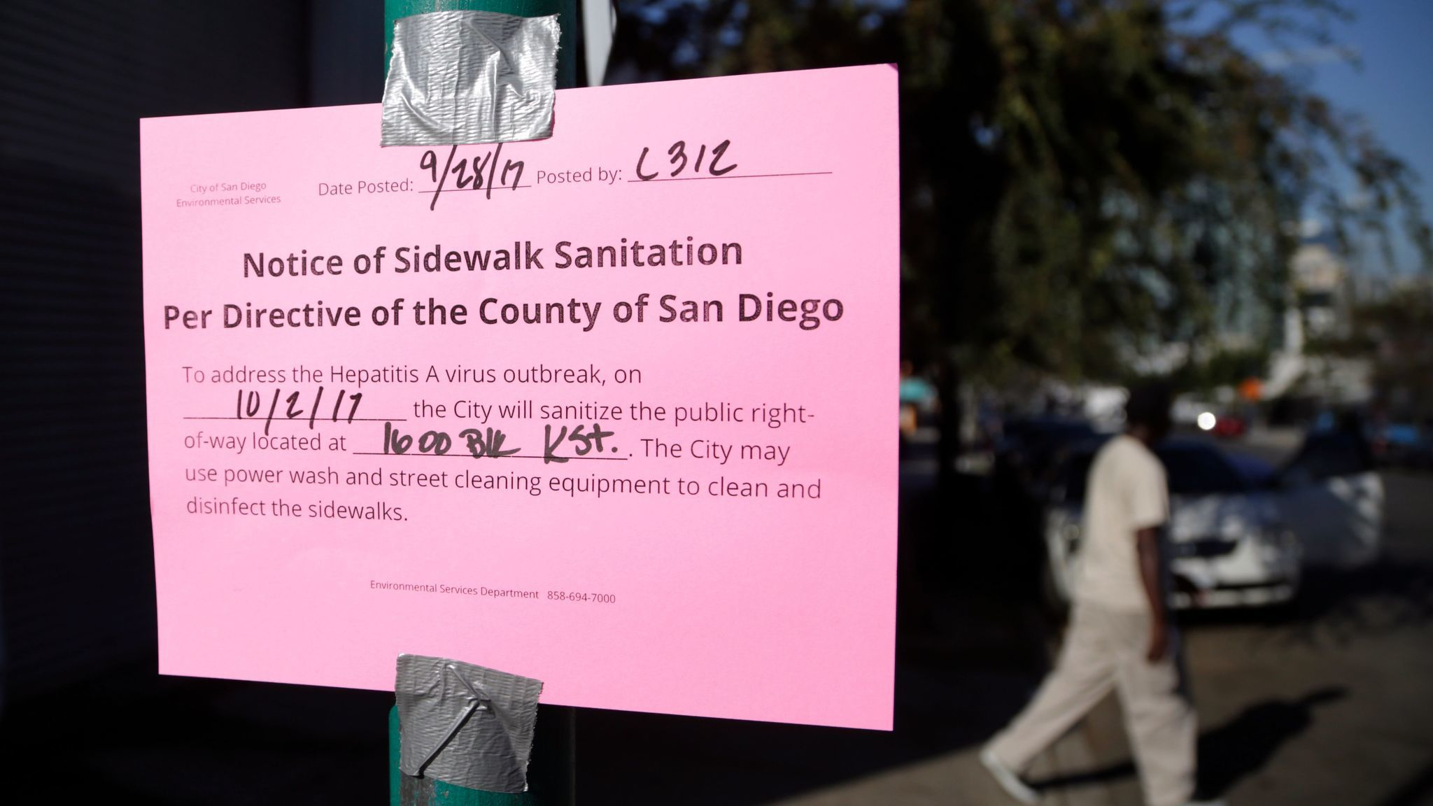 A man passes behind a sign warning of an upcoming street cleaning along 17th Street in San Diego.