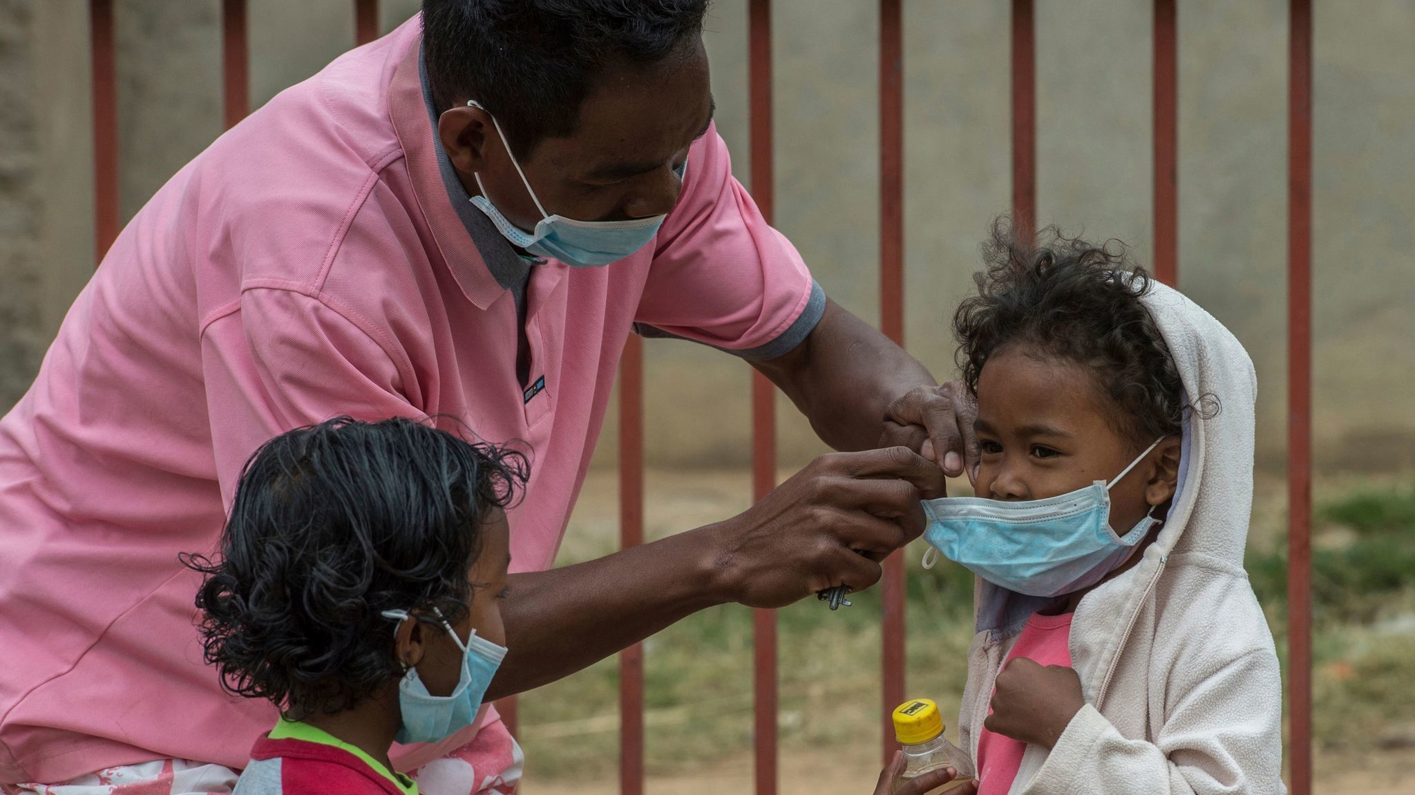 A caregiver places masks on schoolchildren in Antananarivo, Madagascar.