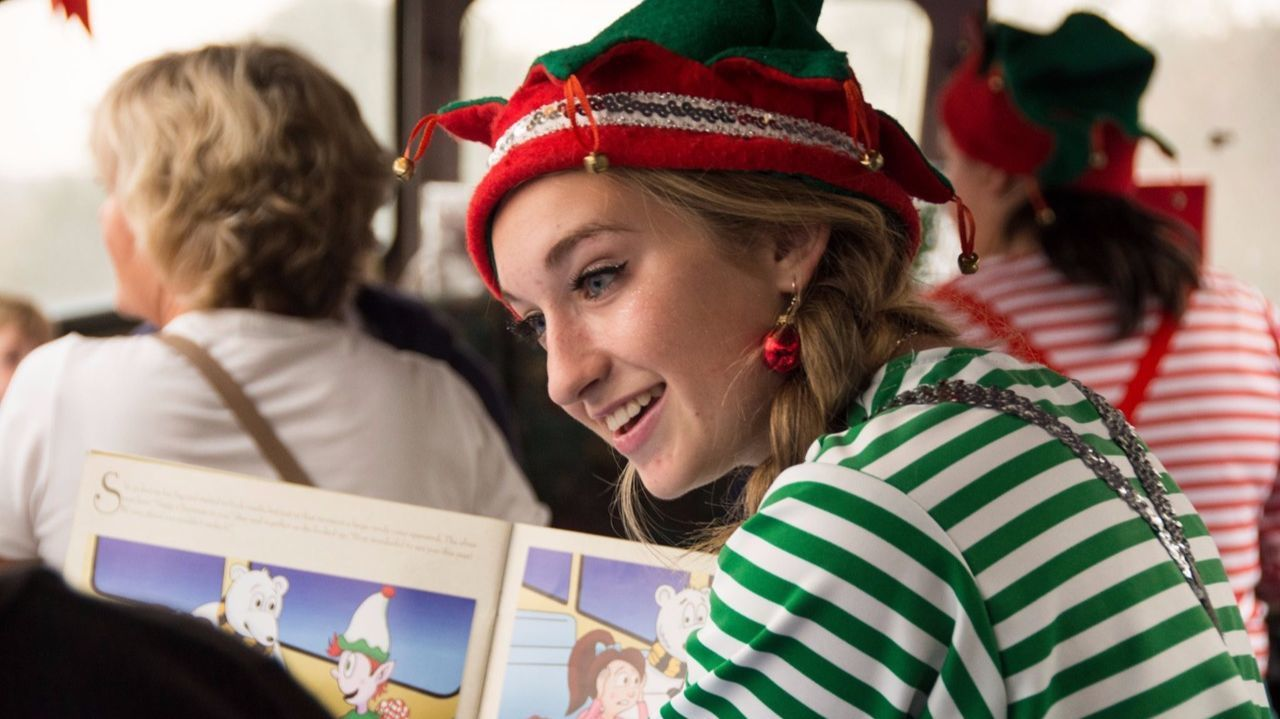 """An elf reads """"The Train to Christmas Town""""  on the Mt. Hood Railroad."""
