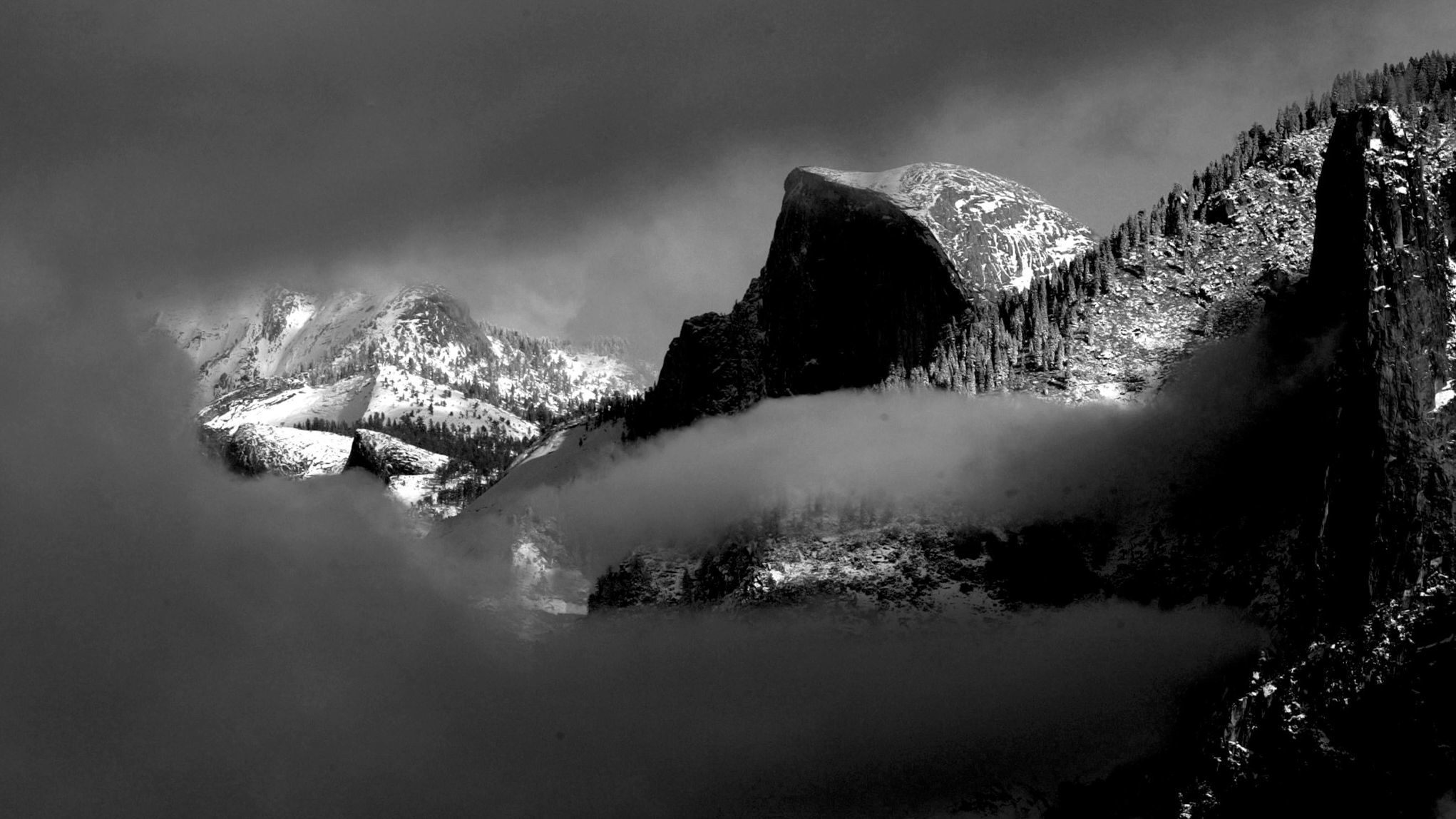 Half Dome peaks out from the clouds.