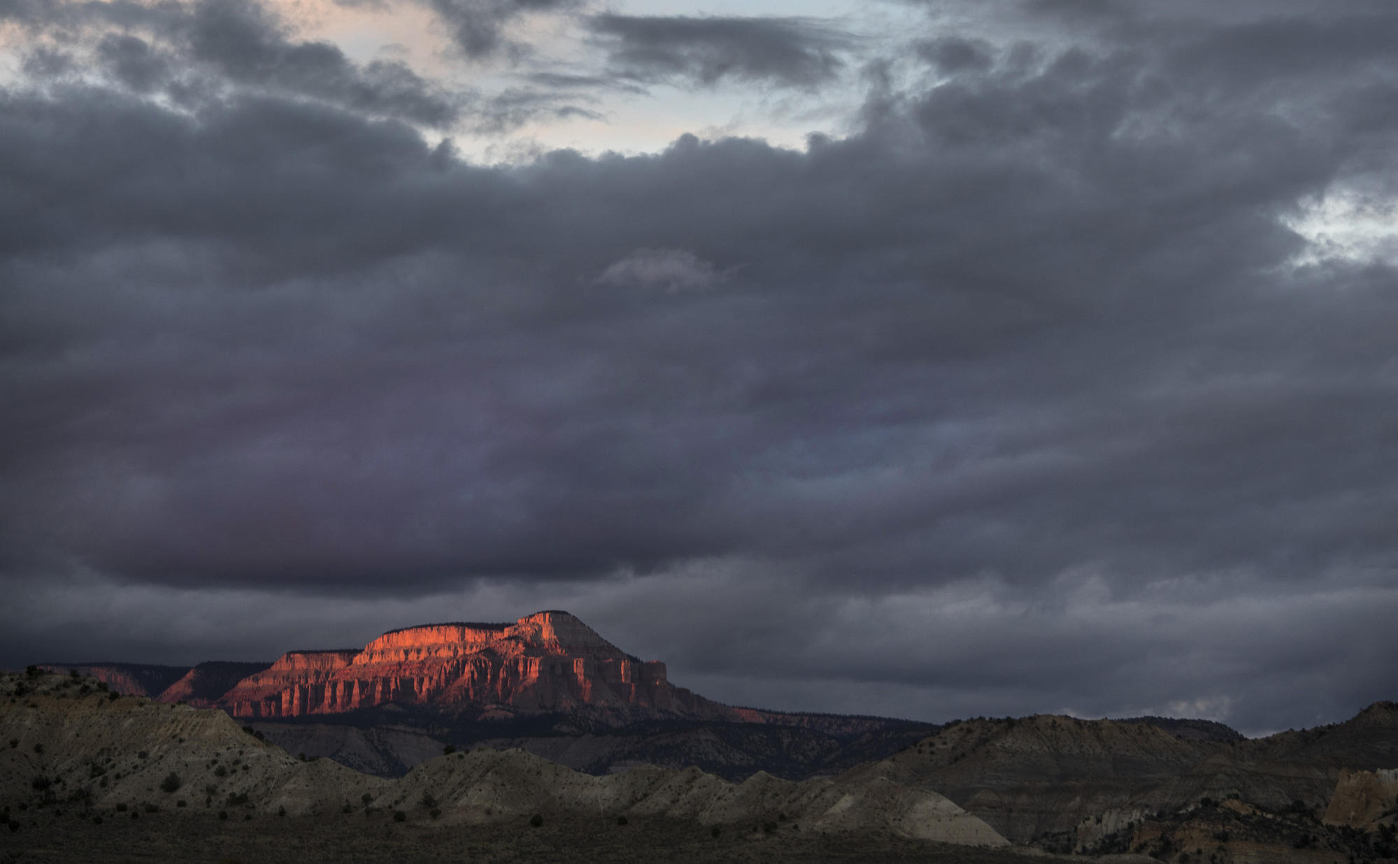 Light from a fading sunset bathes 10,188-foot Powell Point in a view from state Highway 12 near Tropic, Utah, in Grand Staircase-Escalante National Monument.