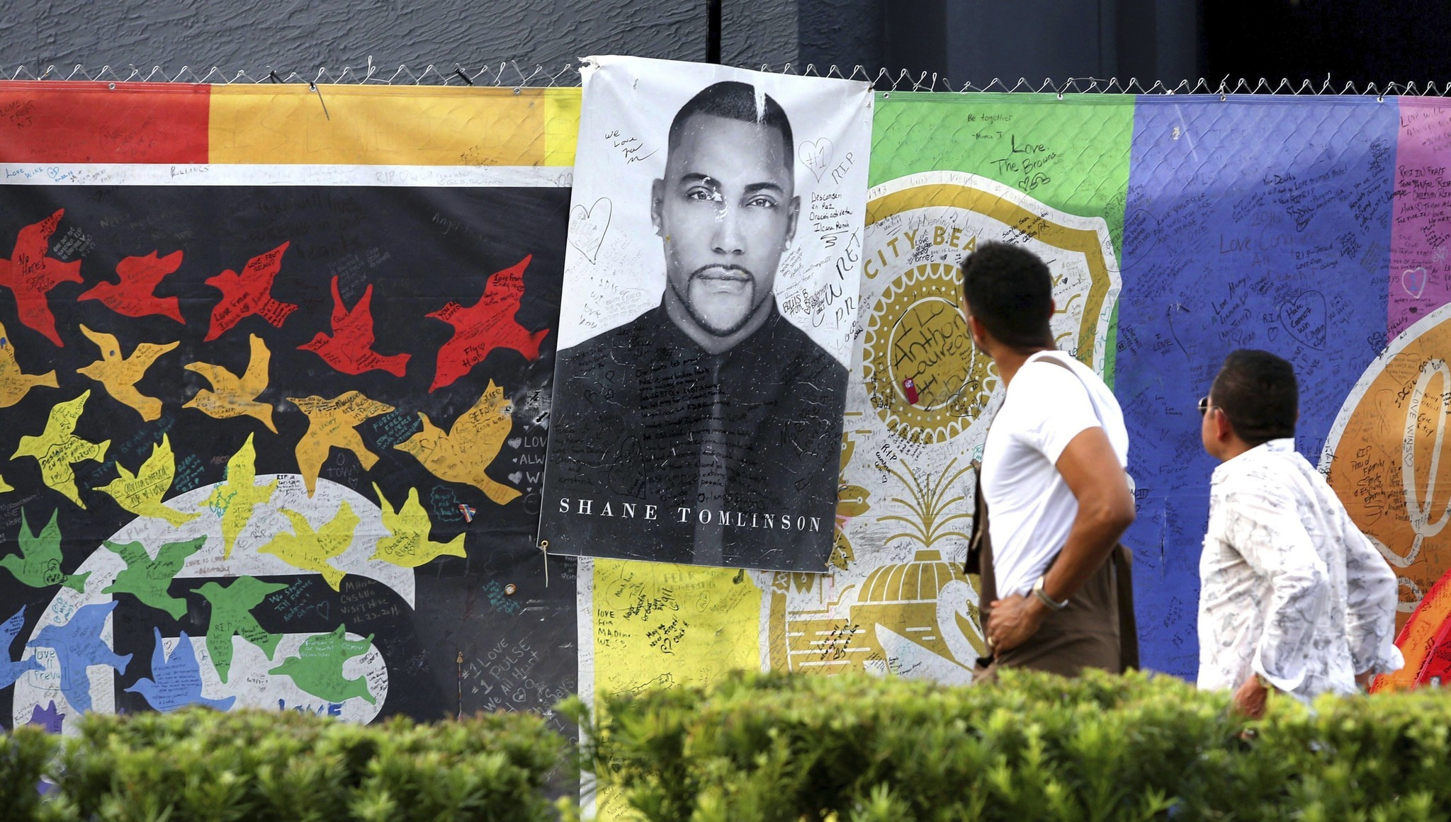 Visitors look at a memorial poster of Pulse nightclub massacre victim Shane Tomlinson at the closed club in Orlando, Fla., on Oct. 2, 2017, a day after the mass shooting Las Vegas.