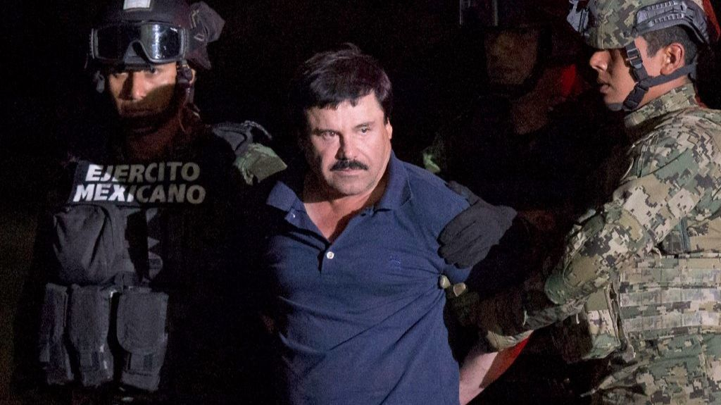 "In this Jan. 8, 2016 file photo, Mexican drug lord Joaquin ""El Chapo"" Guzman is escorted by army soldiers to a waiting helicopter after he was recaptured from breaking out of a maximum security prison in Mexico."