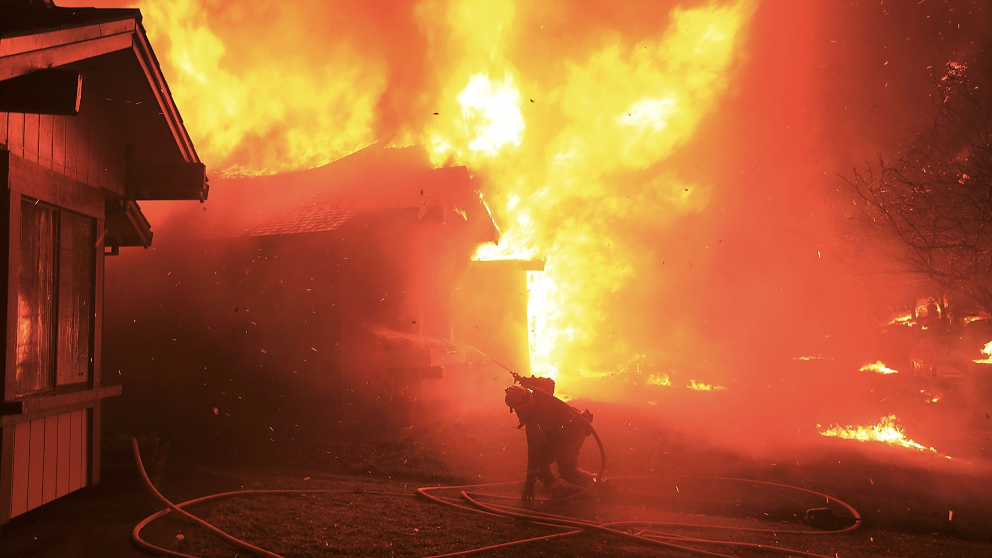 A firefighter struggles to protect a home from flames in Santa Rosa's Coffey Park neighborhood on Oct. 9, 2017.