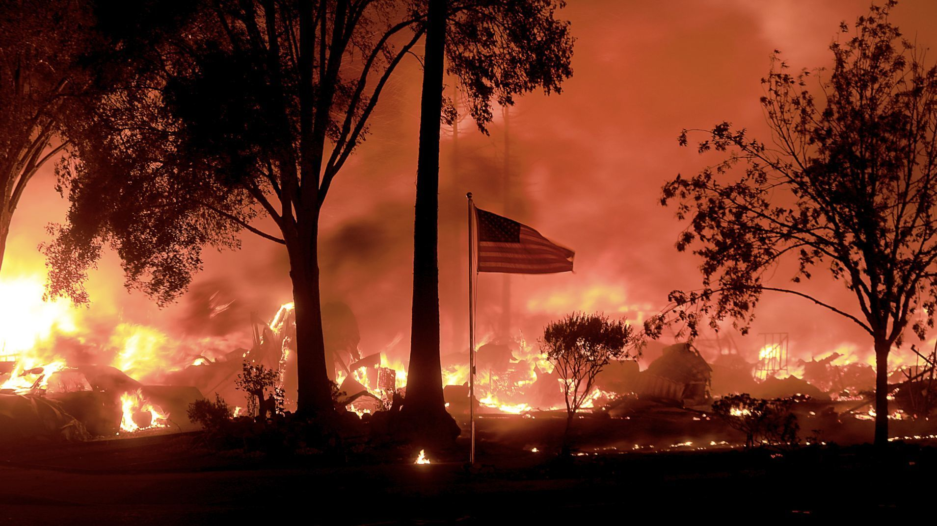 An American flag still flies as structures burn in Coffey Park in Santa Rosa.