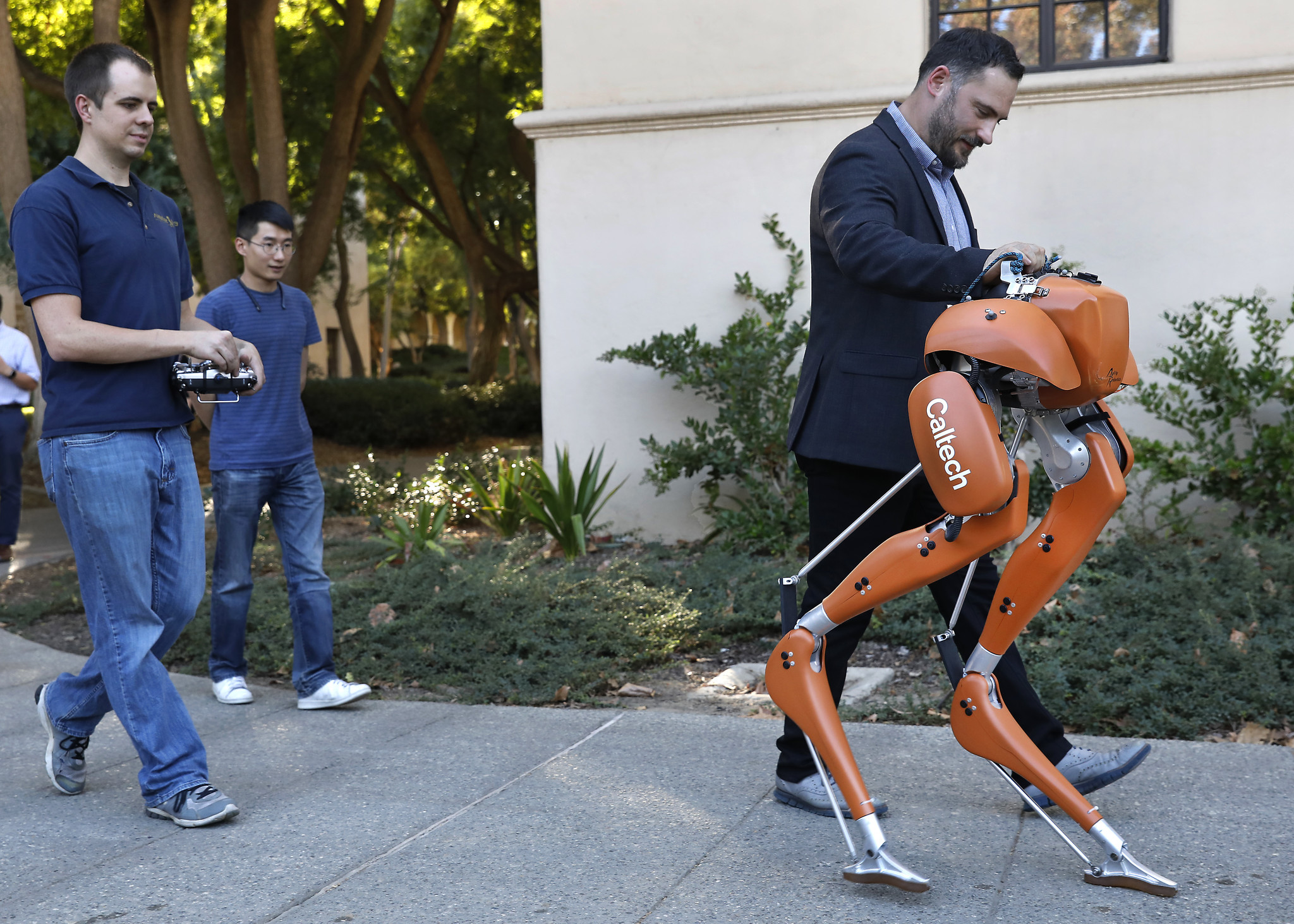 Caltech professor Aaron Ames walks on campus alongside Cassie, a semi-autonomous robot, as doctoral student Jacob Reher, left, controls the direction that Cassie travels. The robot's balance and gait are autonomous.