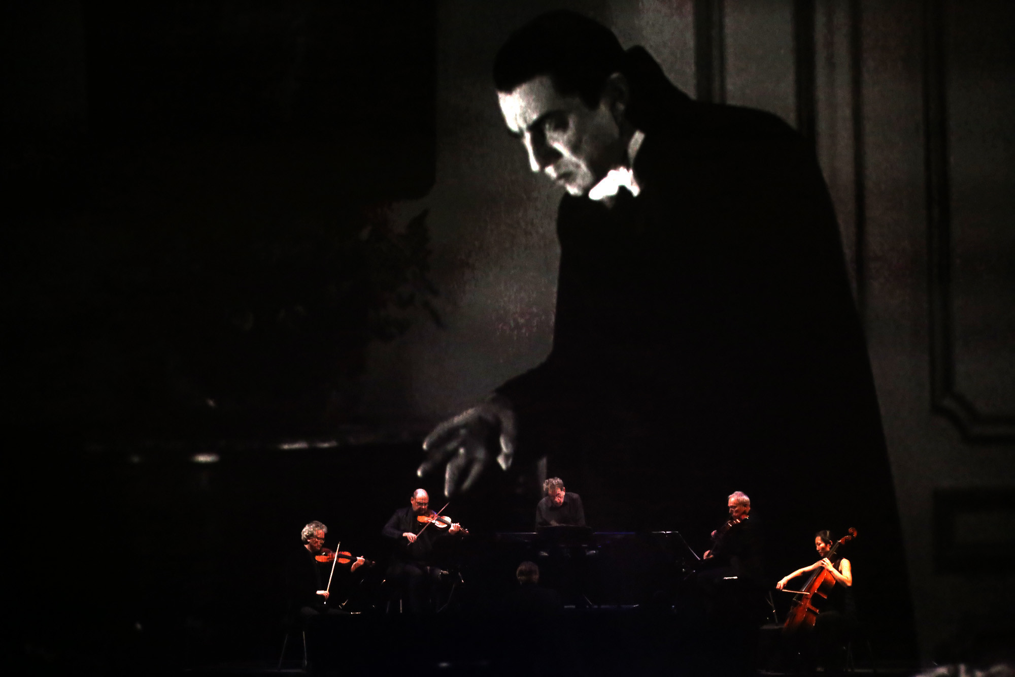 Glass and the Kronos Quartet perform behind a scrim as Bela Lugosi fills the screen at the Ace.
