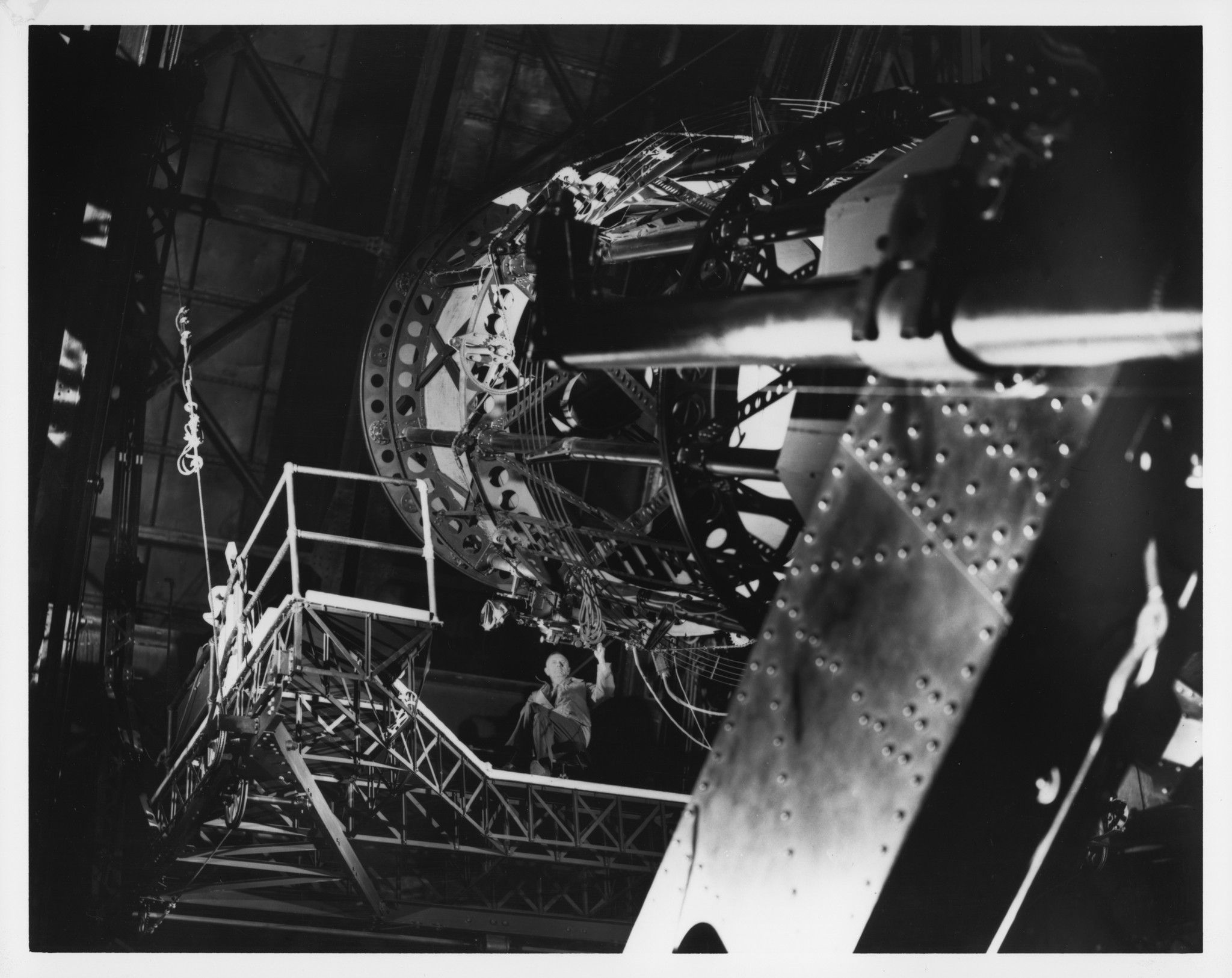 Edwin P. Hubble seated on the Newtonian platform of the Hooker 100-inch reflecting telescope, as viewed from the dome floor, circa 1940.