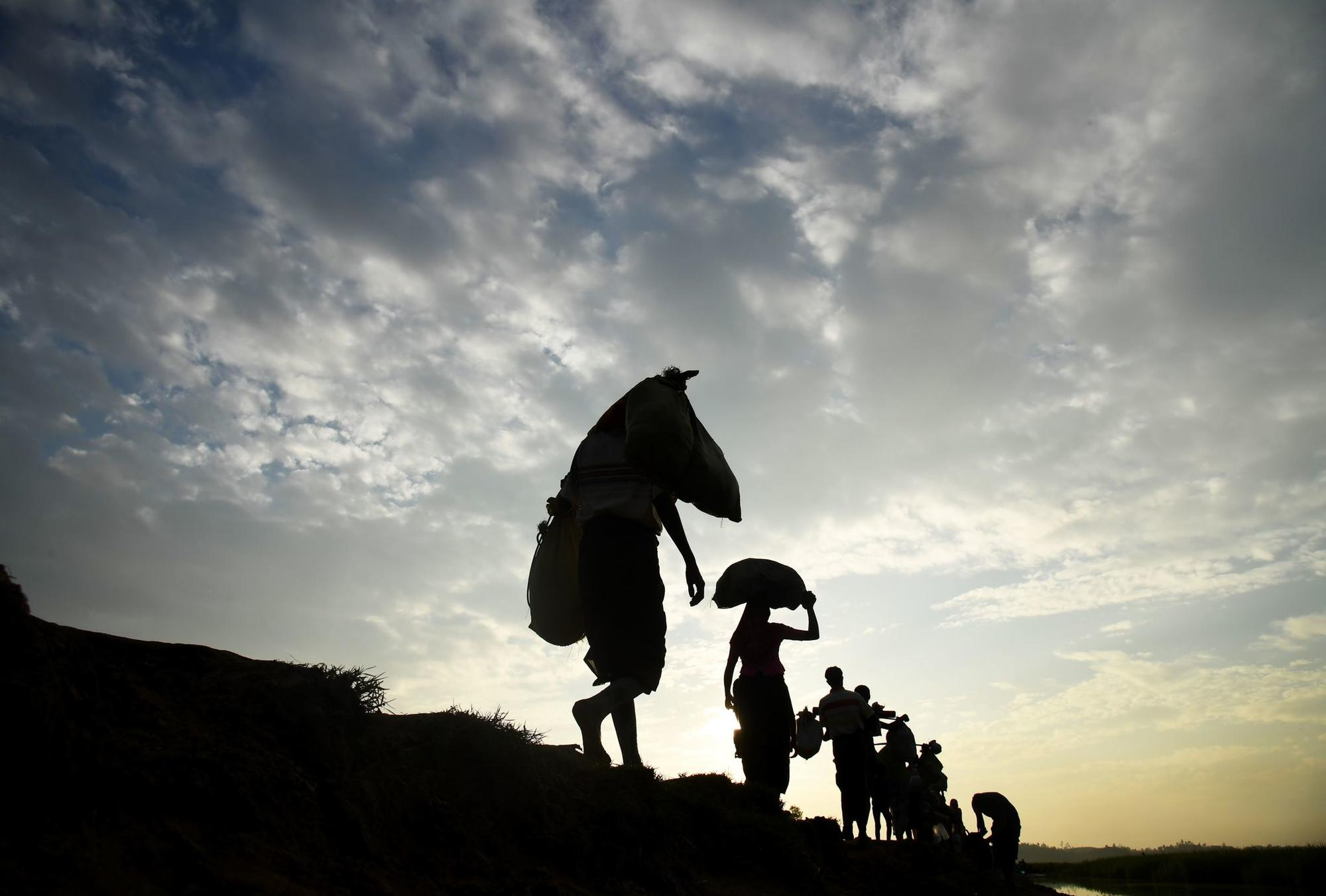 Rohingya Muslim refugees who were stranded after leaving Myanmar walk toward the Balukhali refugee camp after crossing the border in Bangladesh's Ukhia district.