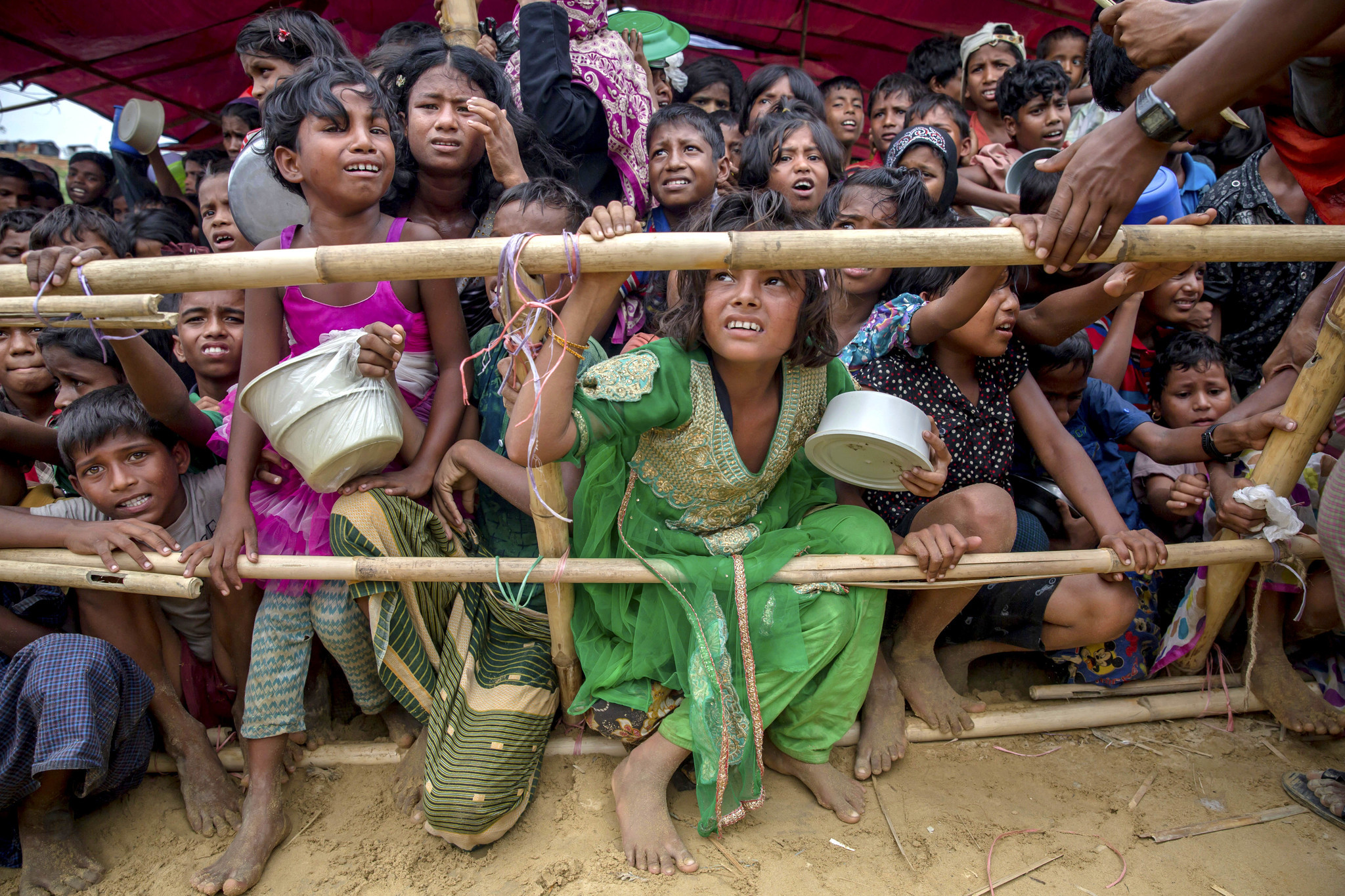 Rohingya Muslim children, who crossed from Myanmar into Bangladesh, wait for their turn to receive food handouts distributed to children and women by a Turkish aid agency at Thaingkhali refugee camp in Bangladesh.