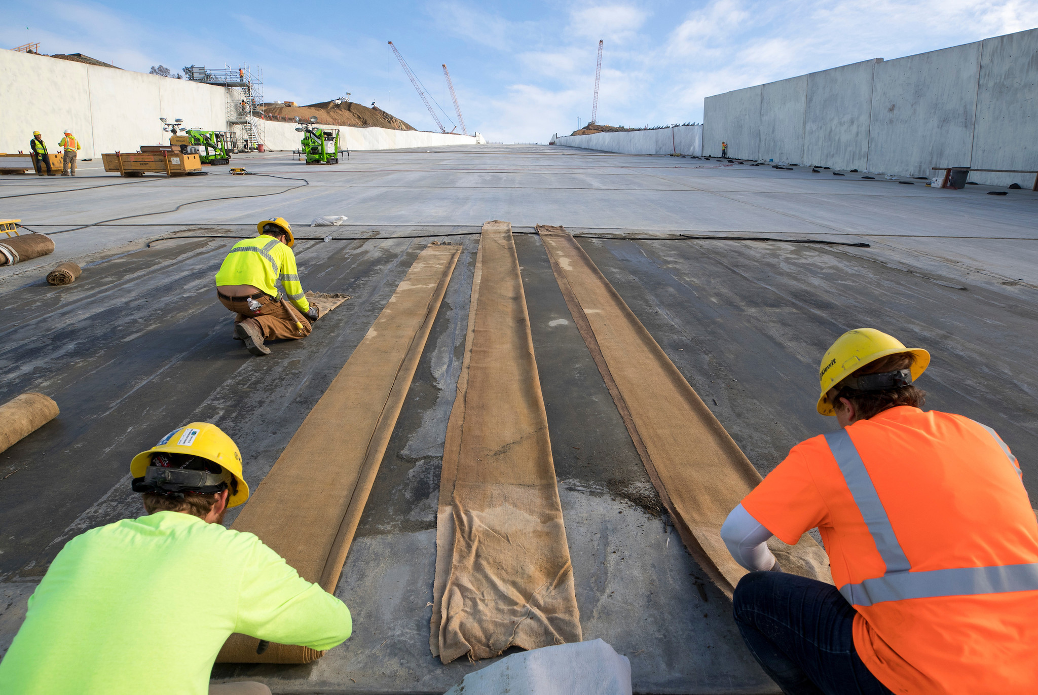 Workers roll up blankets used in the curing process for the structural concrete panels on the lower chute at the Lake Oroville flood control spillway on Monday.