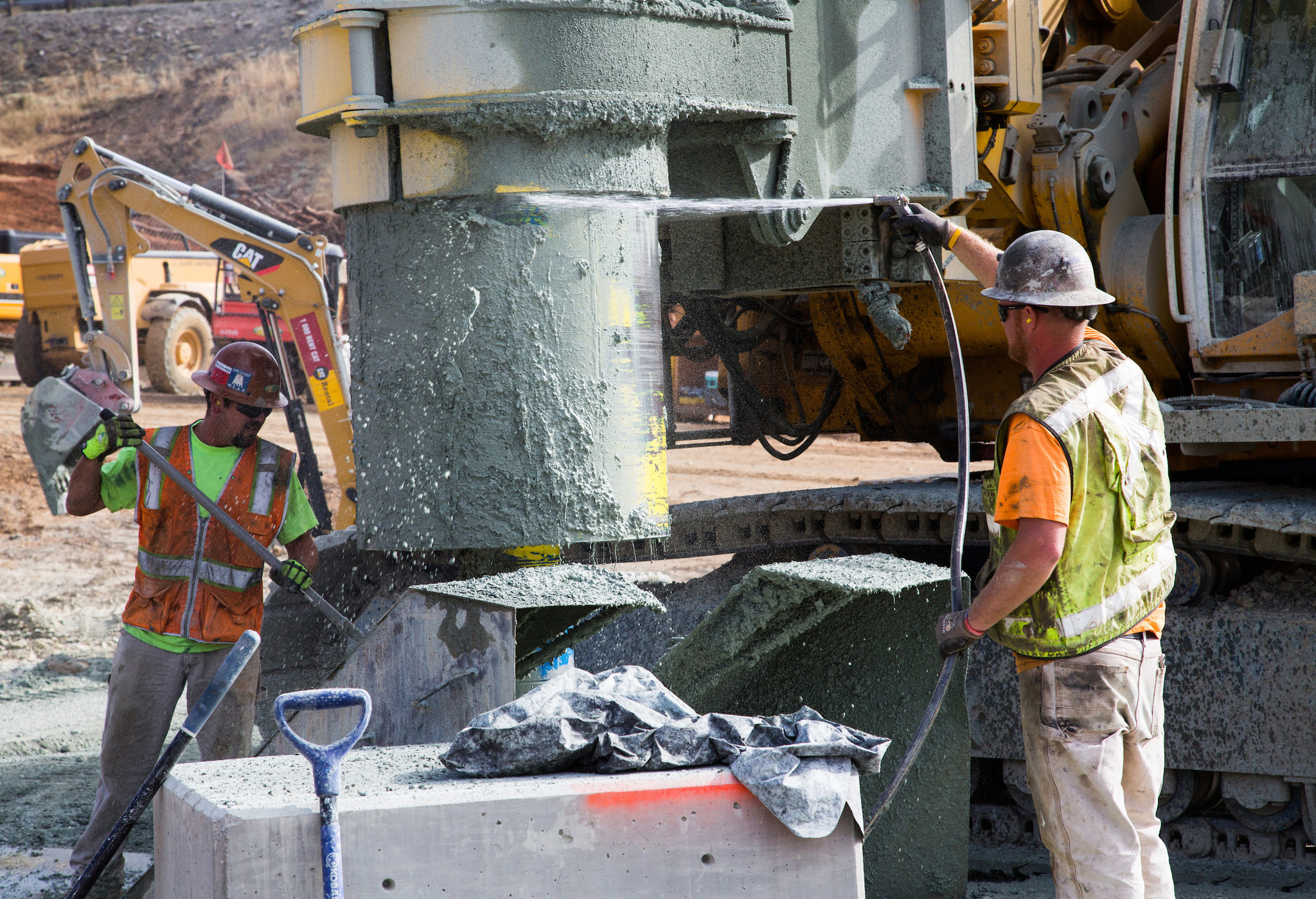 Workers clean the bit of a drilling rig used for drilling holes at the cutoff wall downslope of the Lake Oroville emergency spillway on Aug. 14.