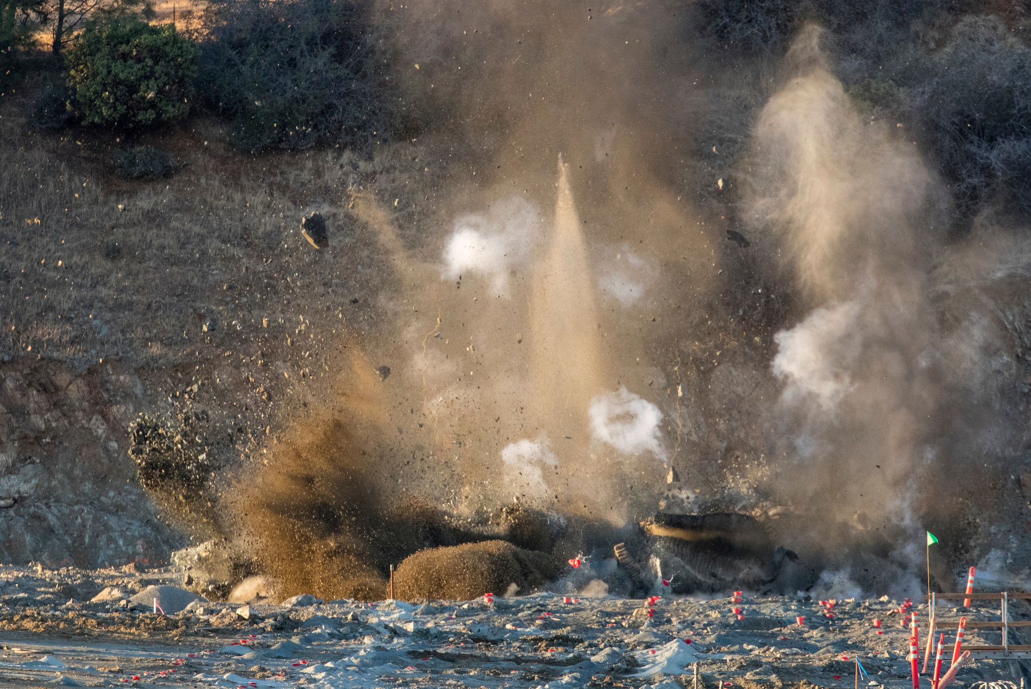 A controlled blast clears rock for the placement of the roller-compacted concrete splashpad downslope from the Lake Oroville emergency spillway on Tuesday.