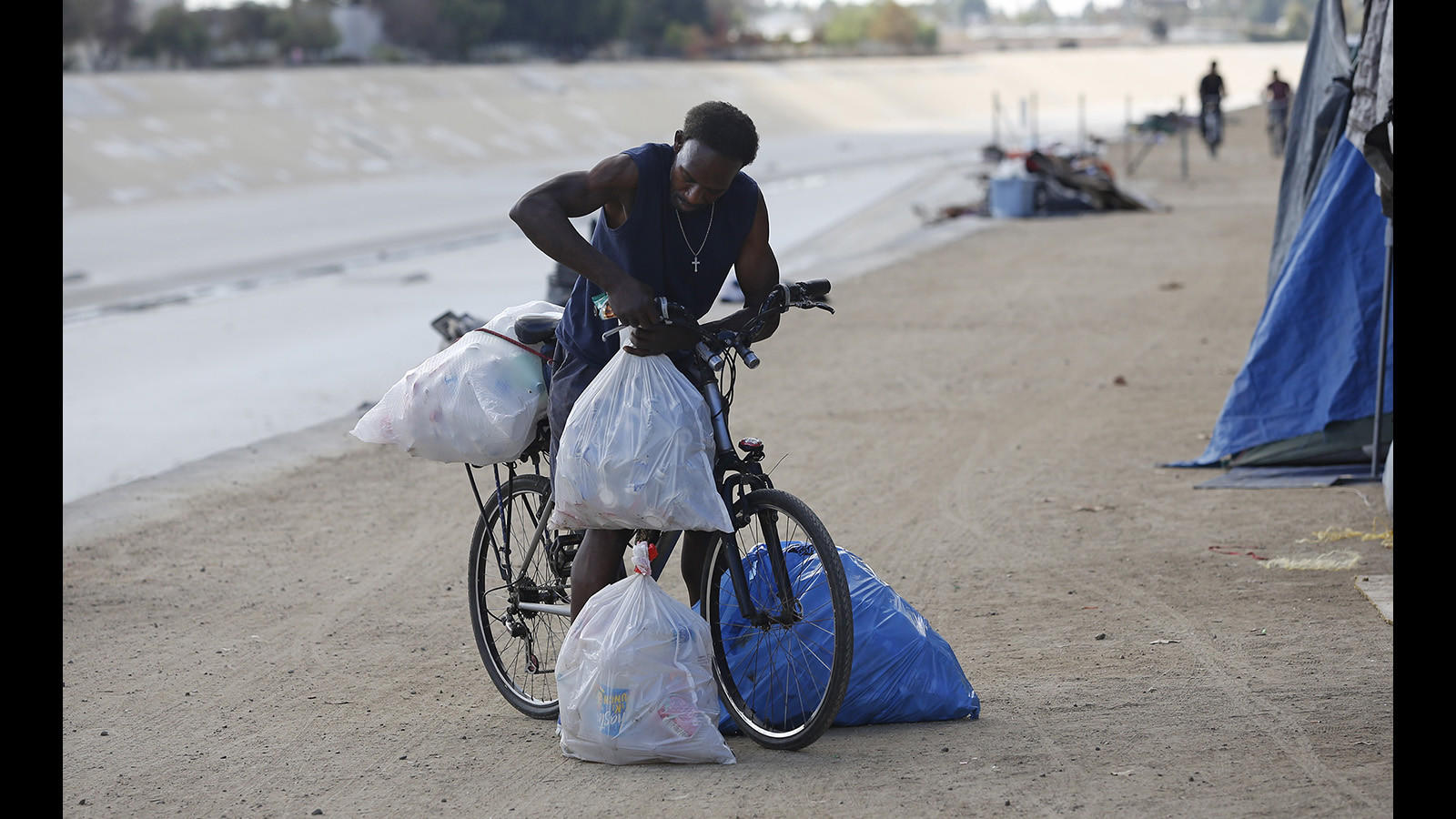 A man readies his belongings and bags of cans at a homeless encampment along the Santa Ana River trail in Fountain Valley.