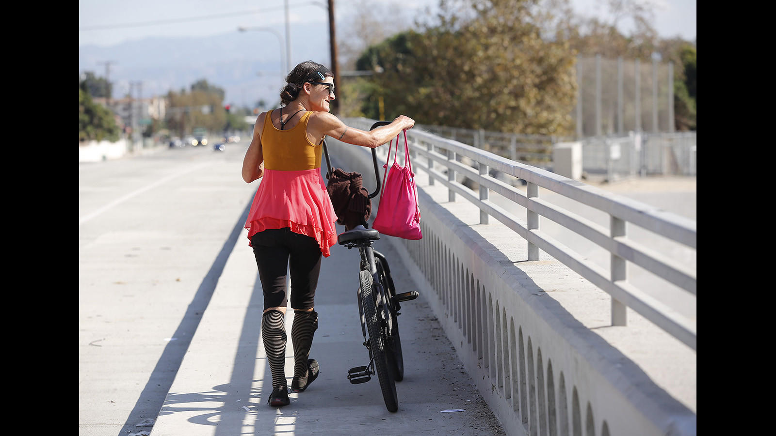 A woman walks past the homeless encampment along the Santa Ana River in Fountain Valley on Thursday.