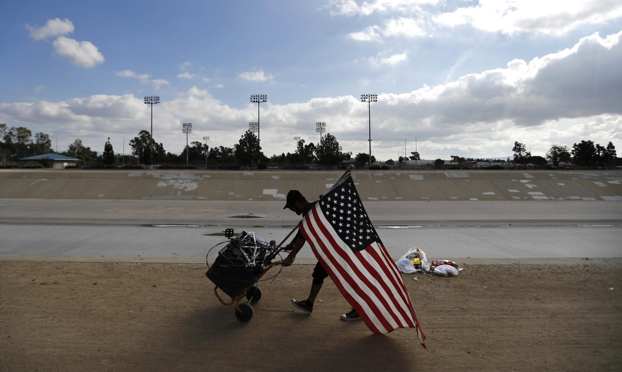 Ivan Reyes, who has been living in the Santa Ana River trail homeless encampment for the past two months, carries an American flag along with his belongings.