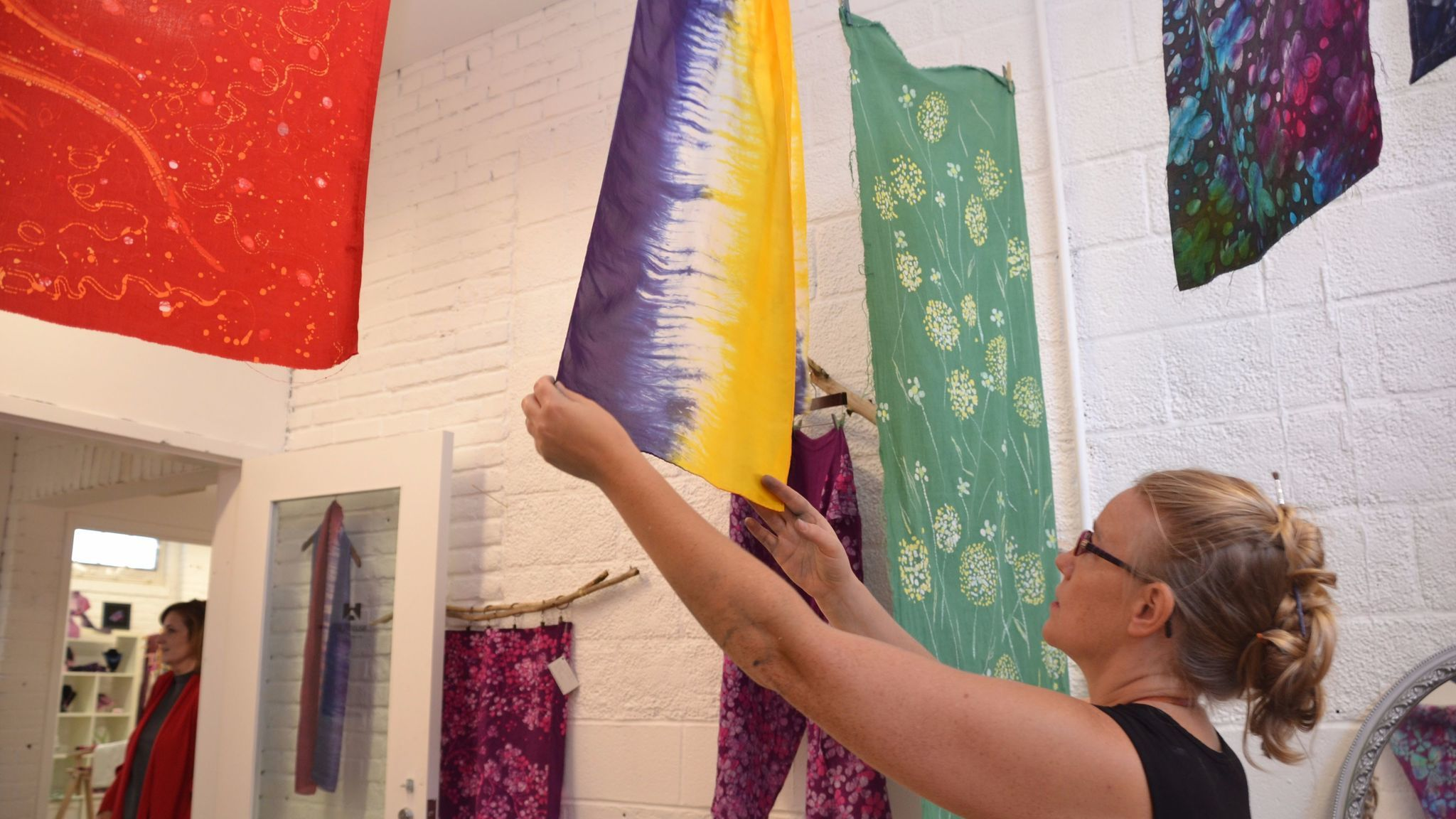 Cheryl VanderMolen Neway, an artist at the Workhouse Arts Center,  looks at a scarf she created using the colors of the National Woman's Party.