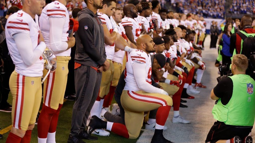 Members of the San Francisco 49ers kneel during the playing of the national anthem before an NFL football game against the Indianapolis Colts,