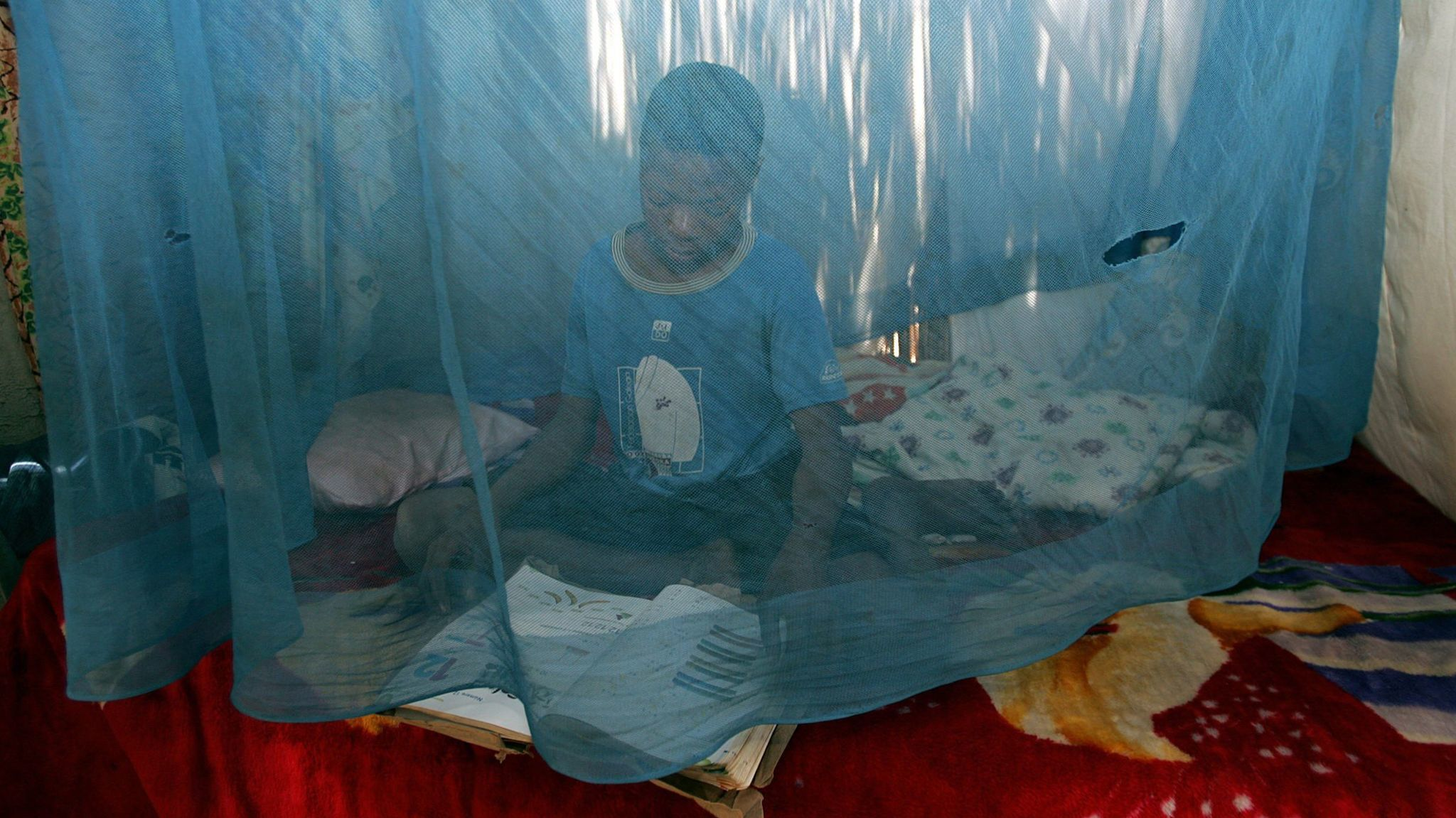 A child sits 22 June 2005 under a mosquito net.