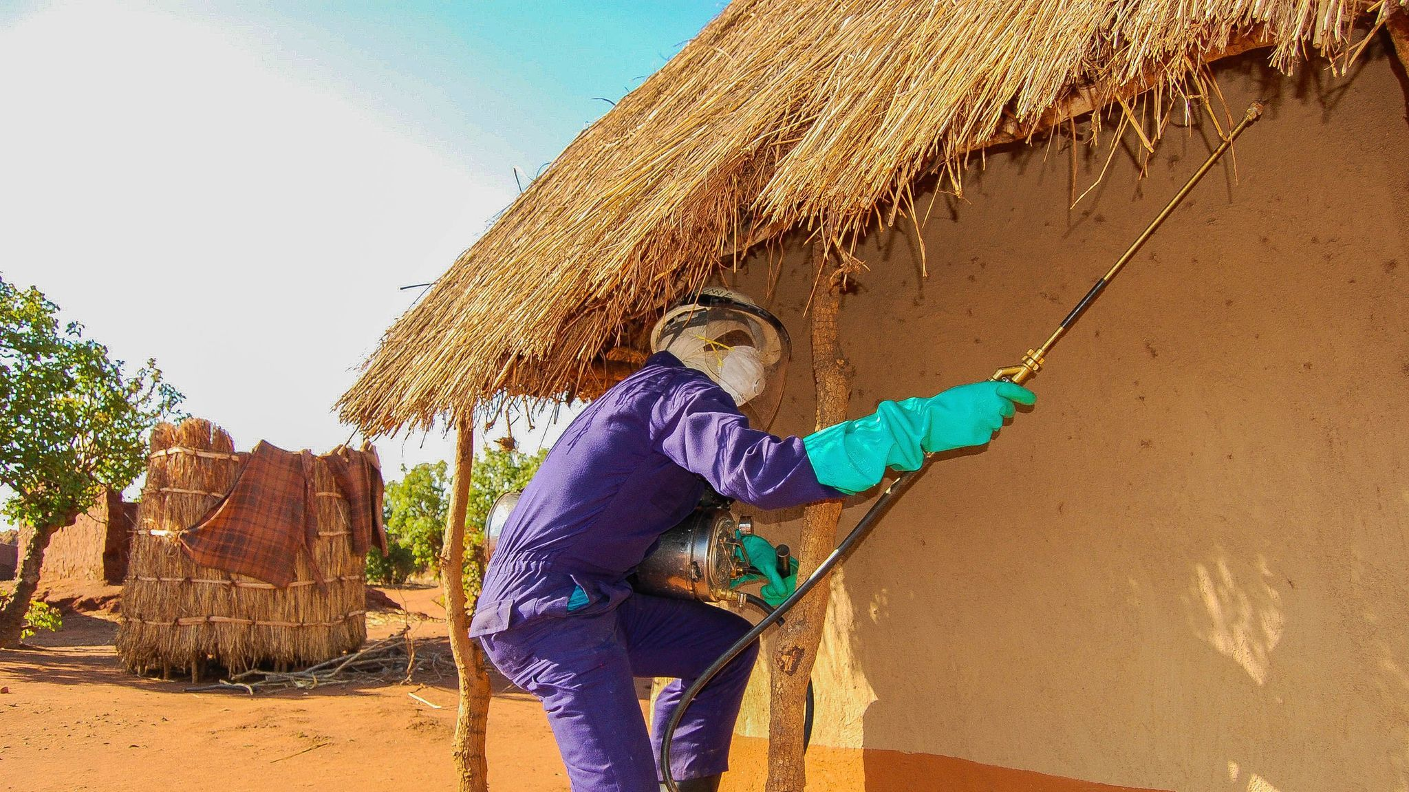 An insecticide sprayer treats a hut.