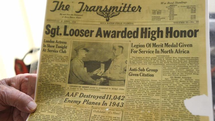 Veteran John Looser shows a newspaper clipping from when he was awarded the prestigious Legion of Me