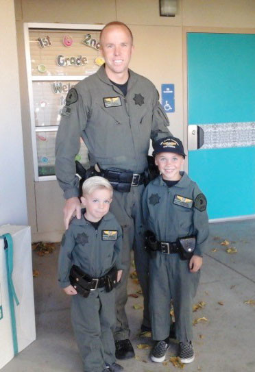 Deputy Chad Dollick with the sheriff's helicopter unit and his sons, Colton and Gavin Dollick, wear matching uniforms.