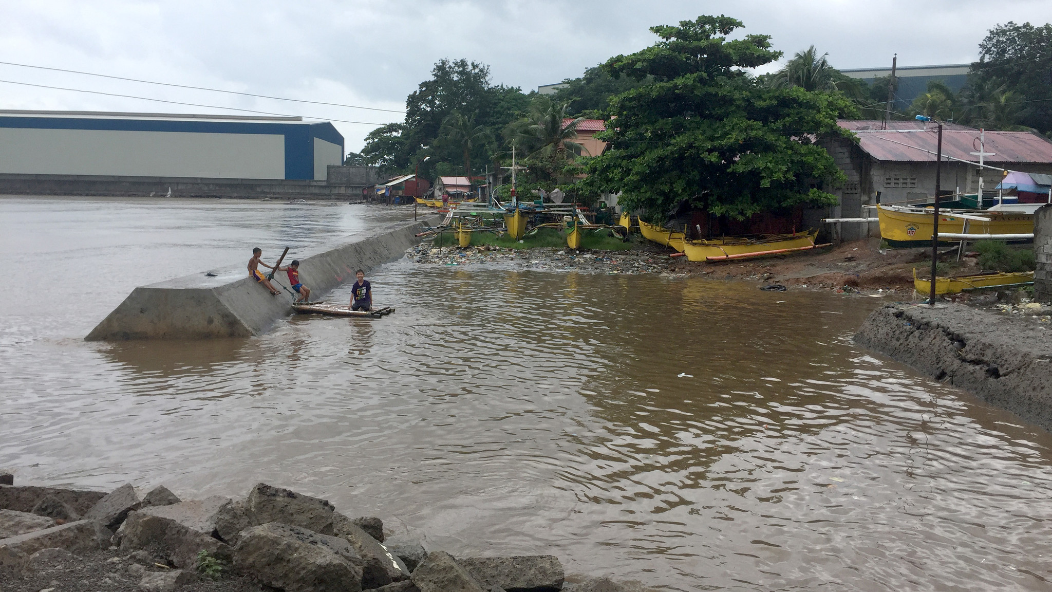 Children swim near the Seafront coal stockpile down the road from Capitan's home.