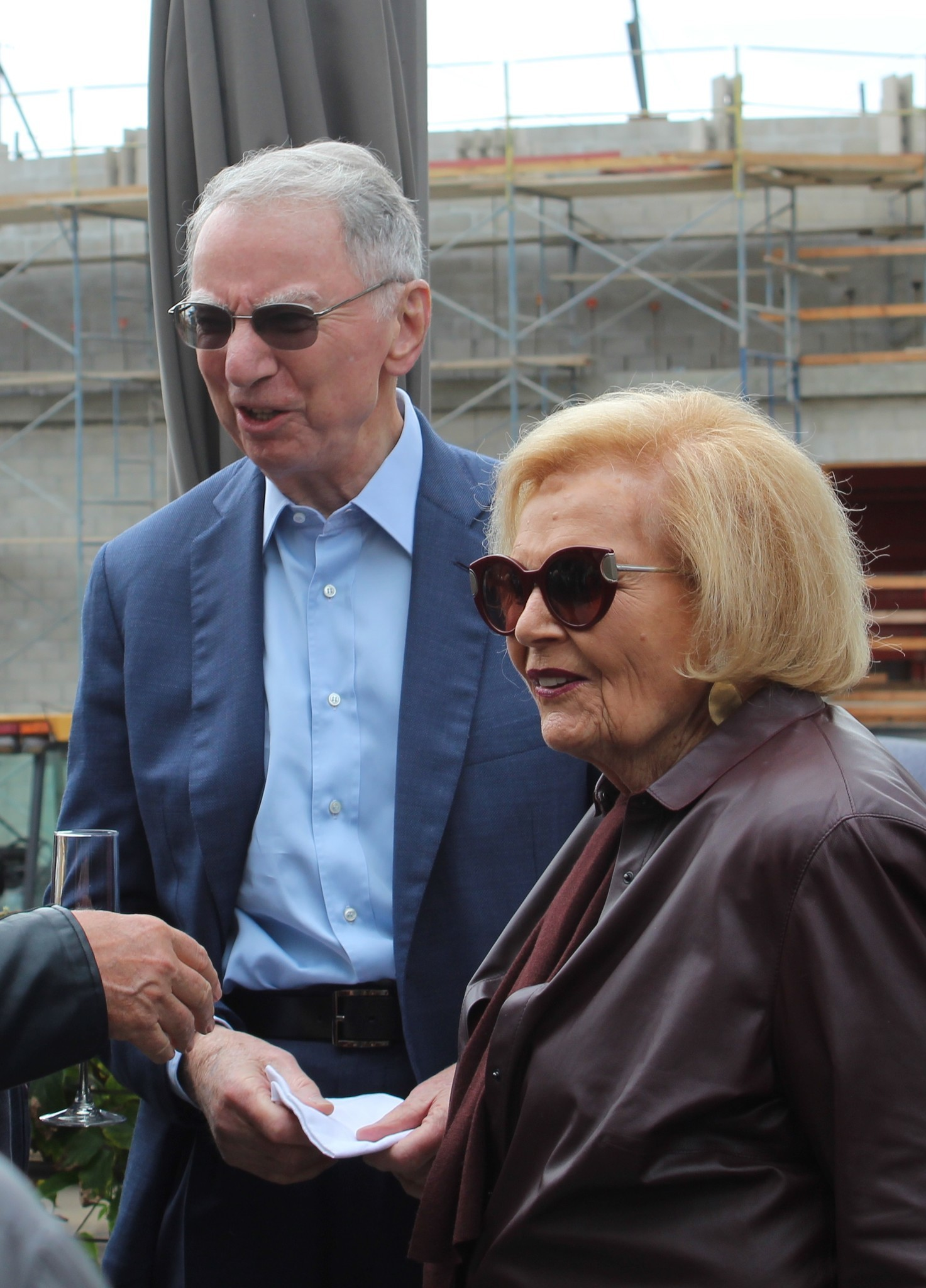 Philanthropists Irwin and Joan Jacobs chat with friends at The Conrad topping-off viewing party on the deck of The Lot movie theater.