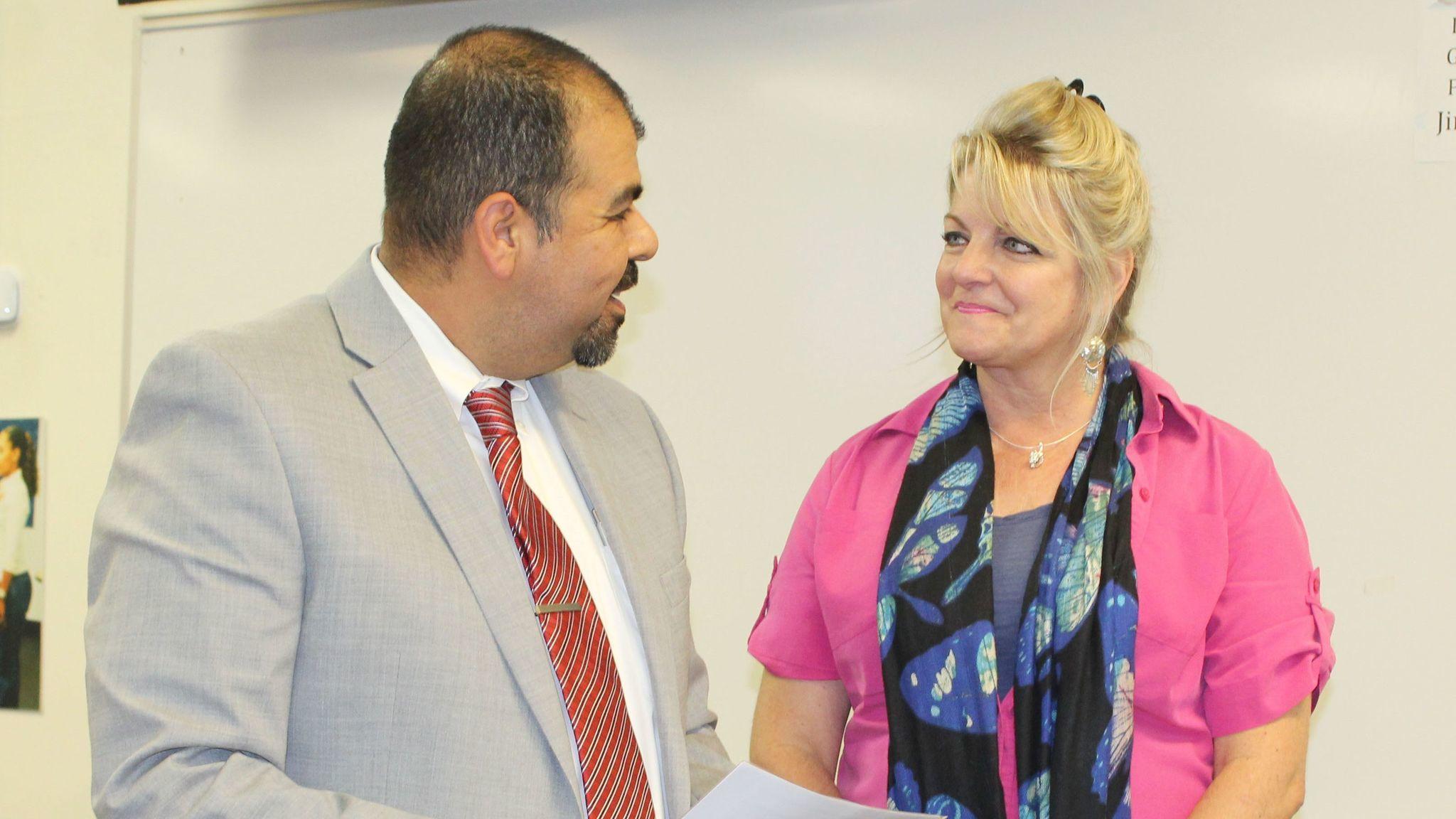 Assistant Superintendent of Human Resources Joel Garcia congratulates teacher Karin Yuhl on her retirement.