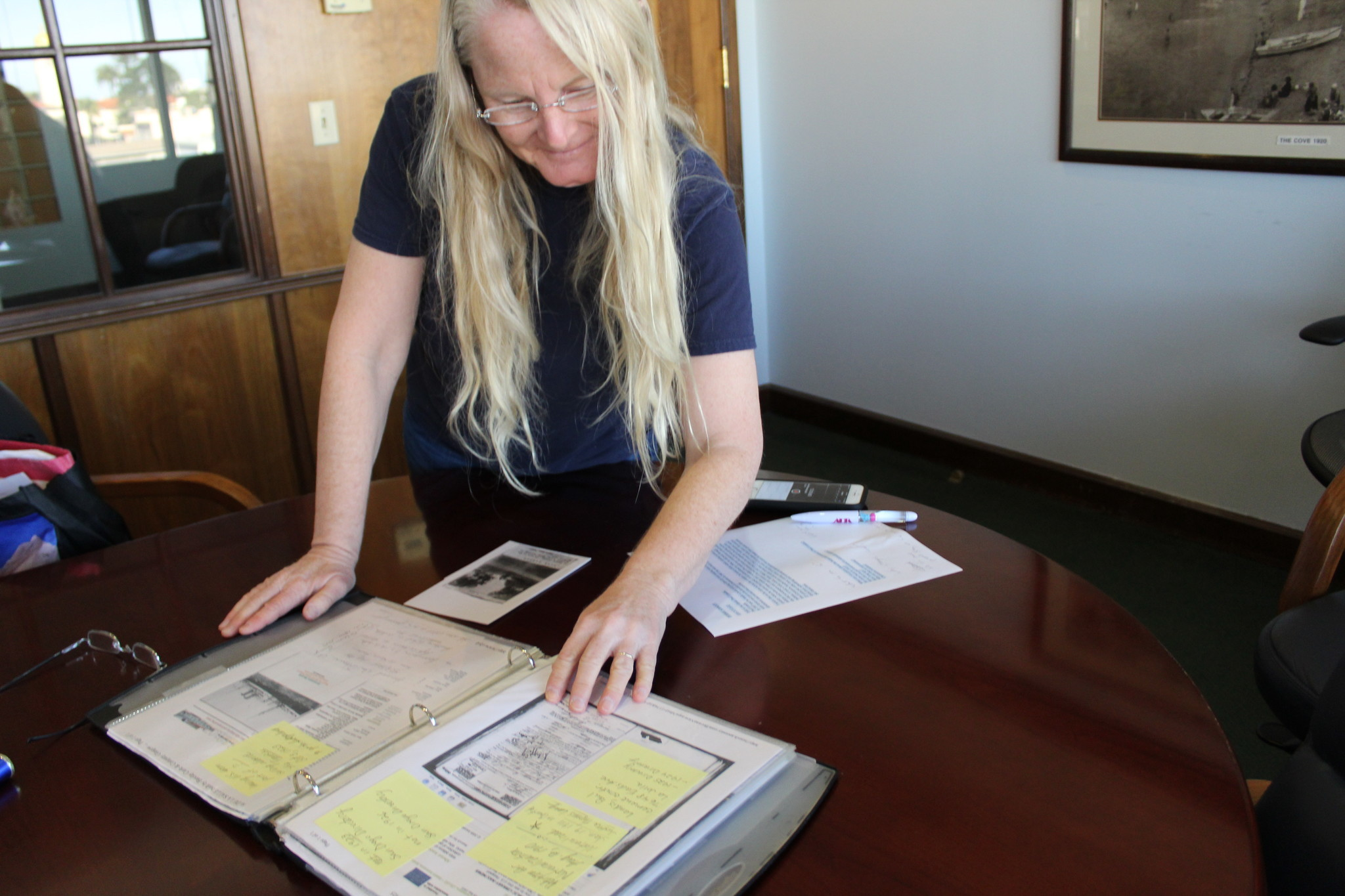 Clairemont resident and sidewalk stamp enthusiast Debbie Abbott looks through her scrapbook of historical information she collects about the cement contractors.