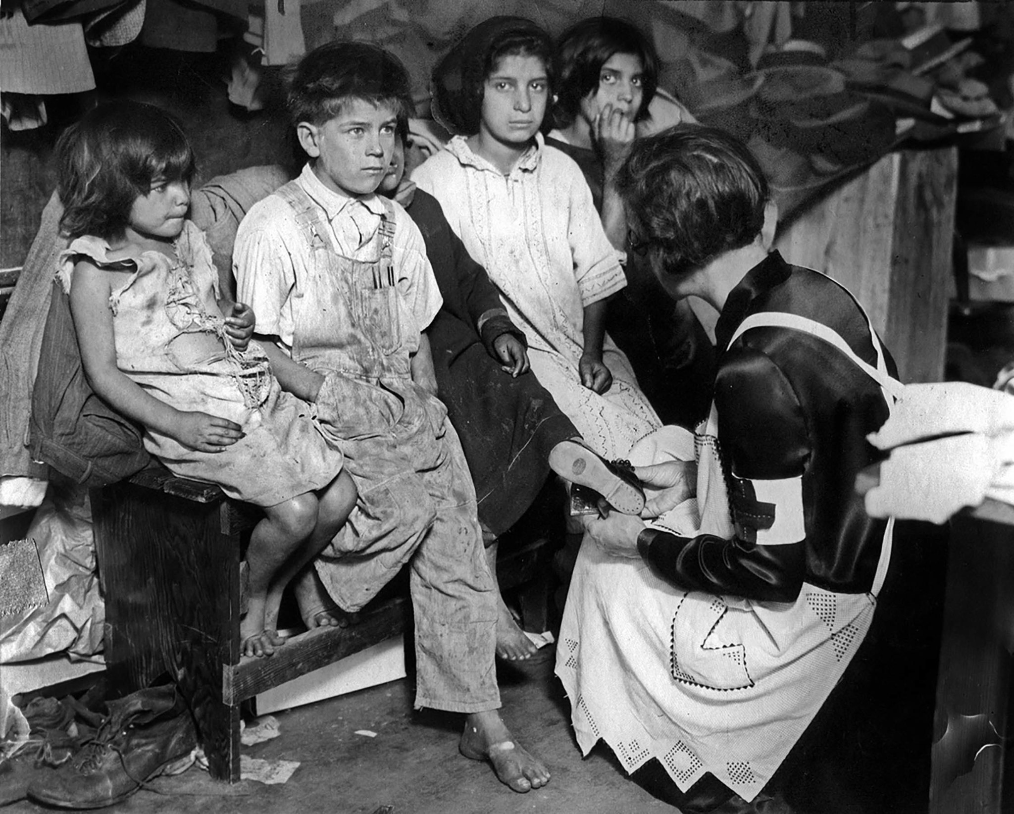 Mar. 14,1928: Red Cross worker helps outfit destitute children after collapse of St. Francis Dam. Th