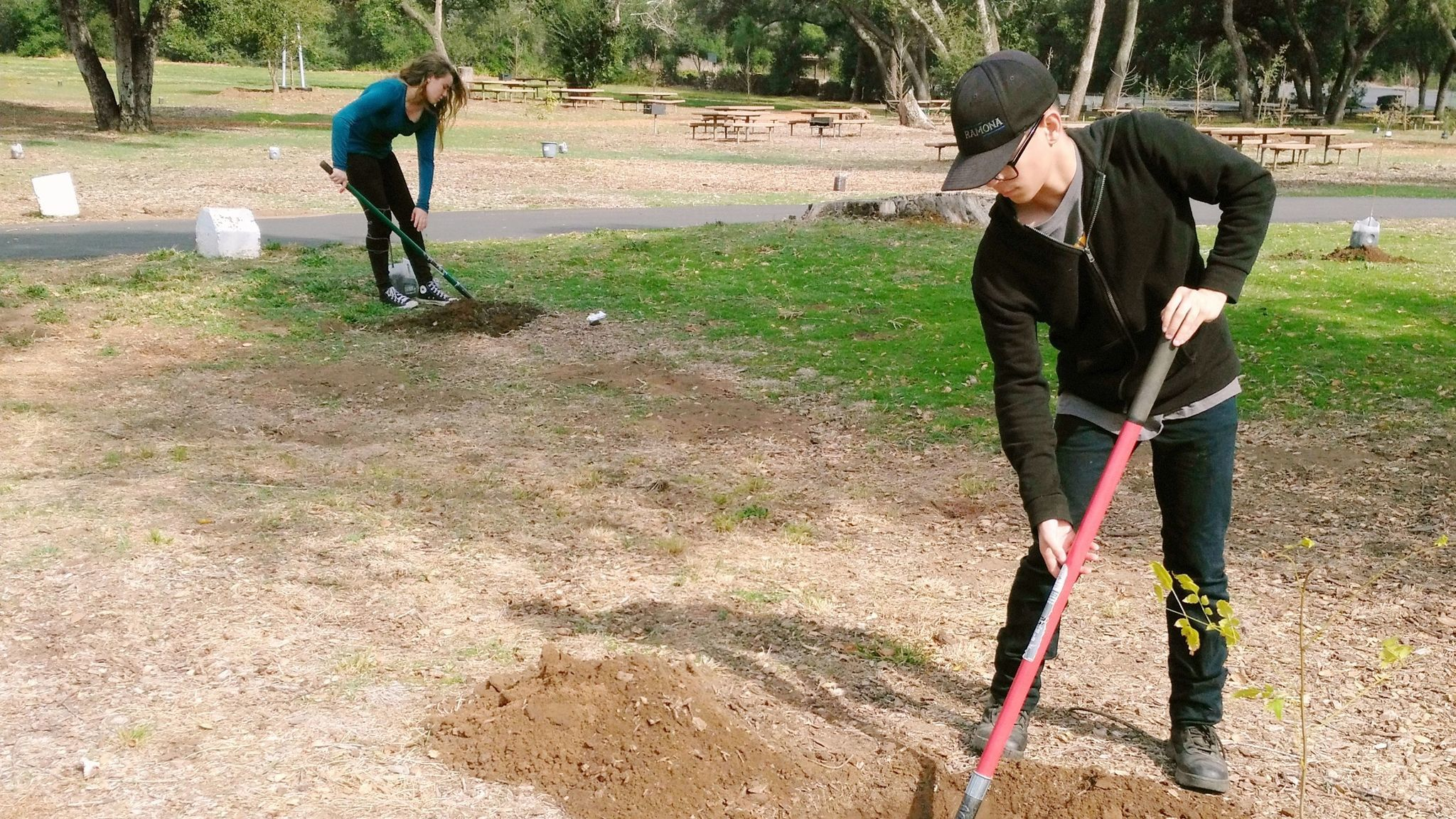 Sydney Marshall, 15, and Aiden Valverde, 14, are among Ramona High School students digging holes for new trees at Dos Picos County Park.