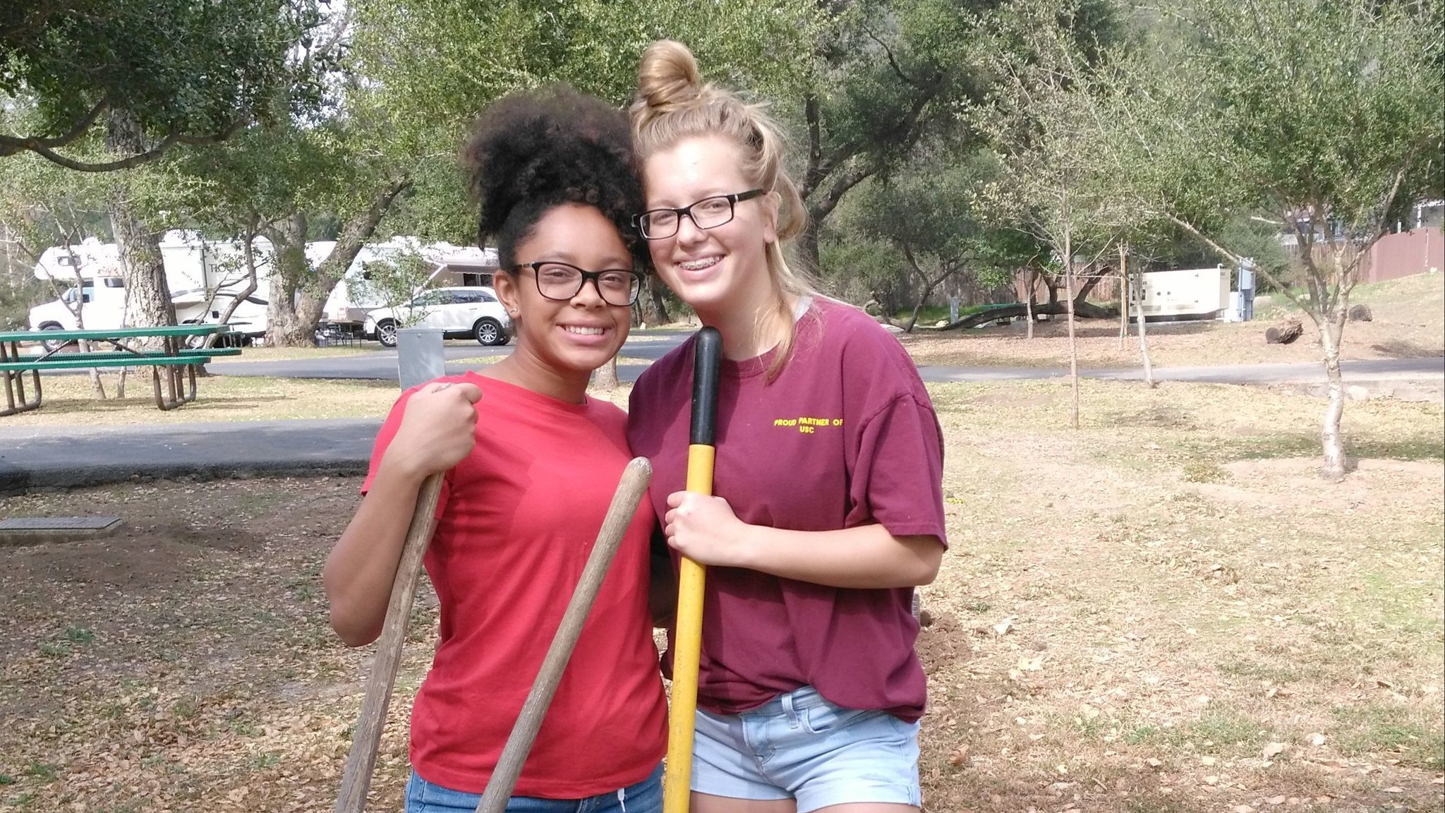 Ramona High School students Ericka Bradley, 15, and Ariel Olvera, 14, use teamwork while planting young trees Saturday in Dos Picos County Park.