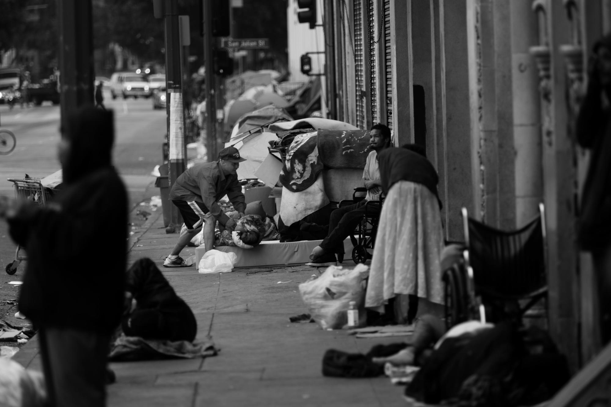 A man rolls up his bed on Skid Row.