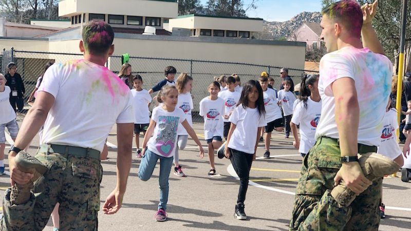 Volunteers from Marine Corps Air Station Miramar douse James Dukes Elementary students with color at the starting line of the 2018 fundraiser that netted approximately $20,480 fo
