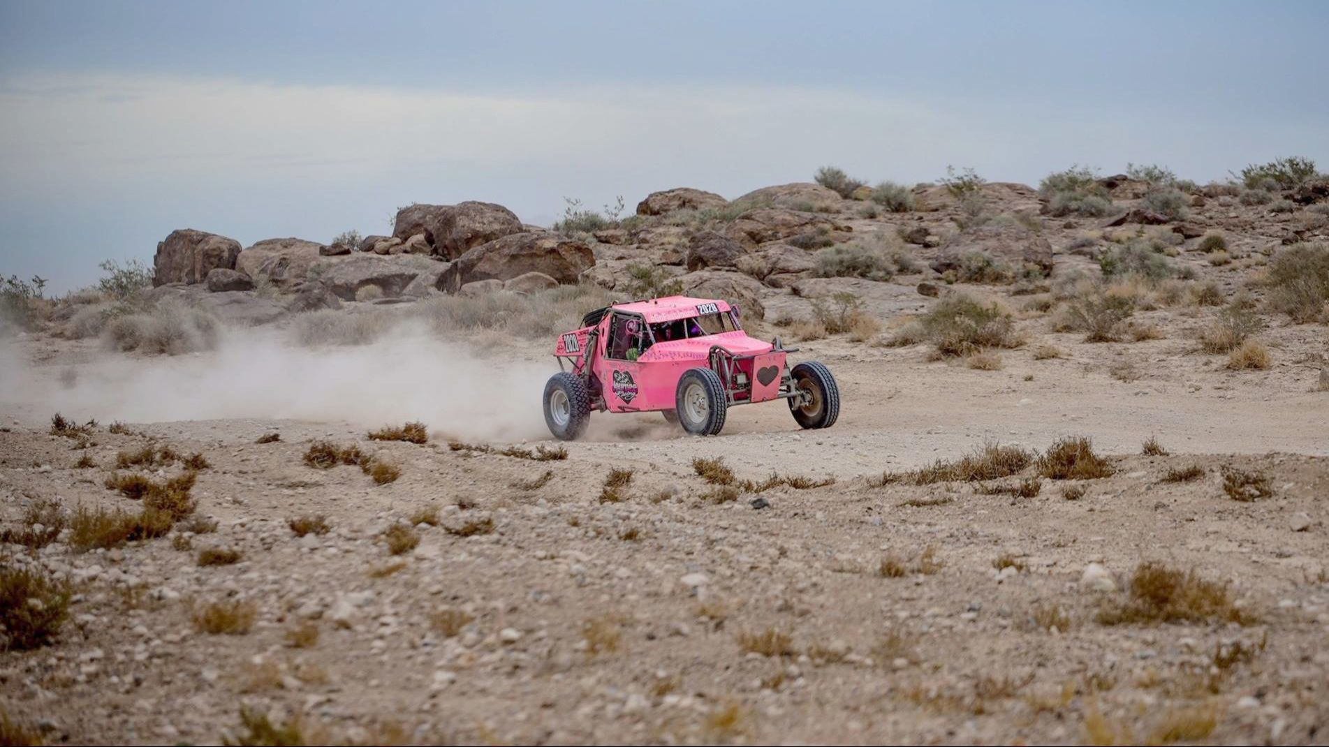The Journey Racing's pink ½ 1600 buggy races through the desert. The off-road racing team supports breast cancer awareness as well as competes in races.
