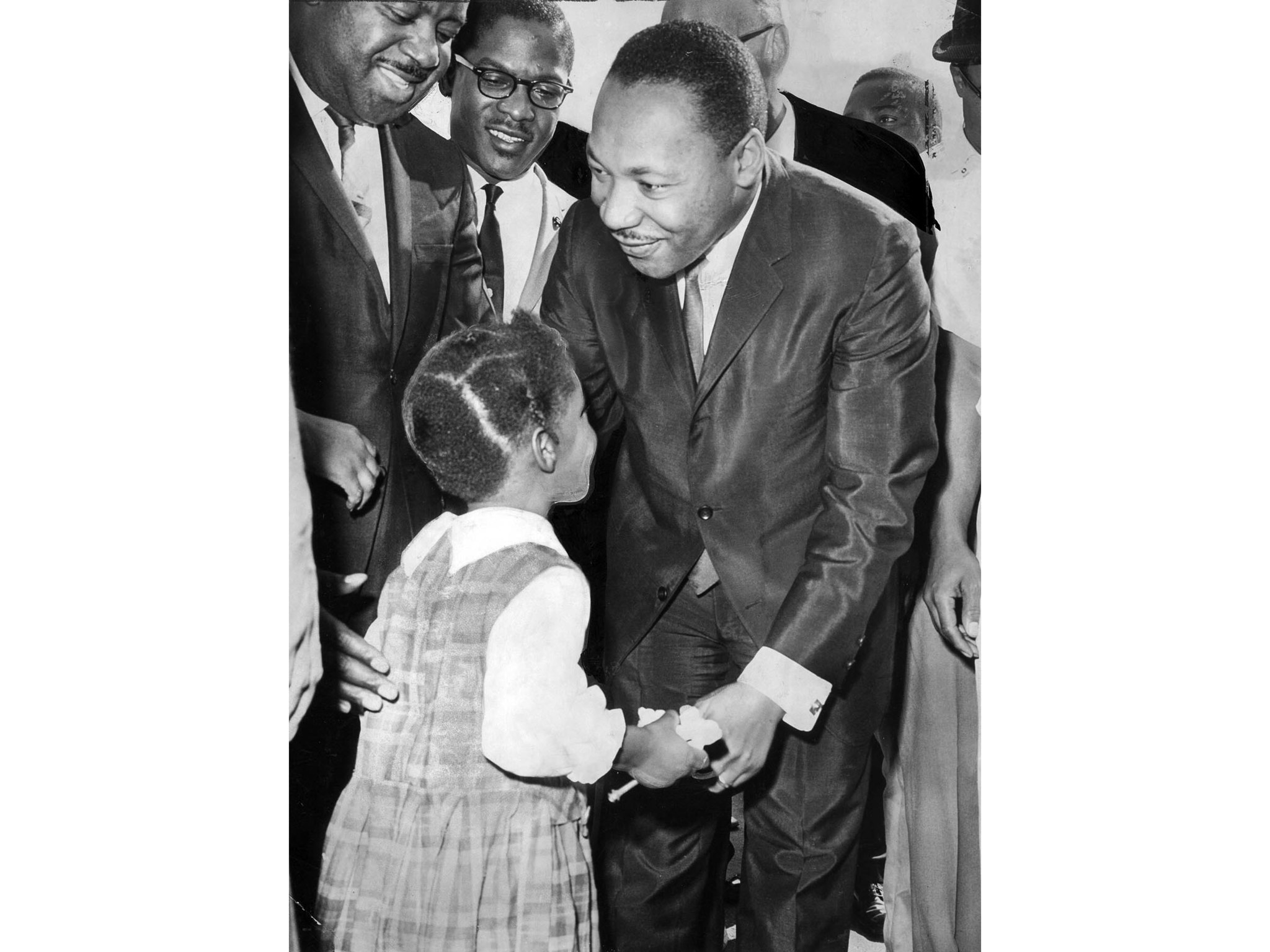 Oct. 27, 1964: Martin Luther King Jr. pauses to chat with young girl during a tour of the Nickerson