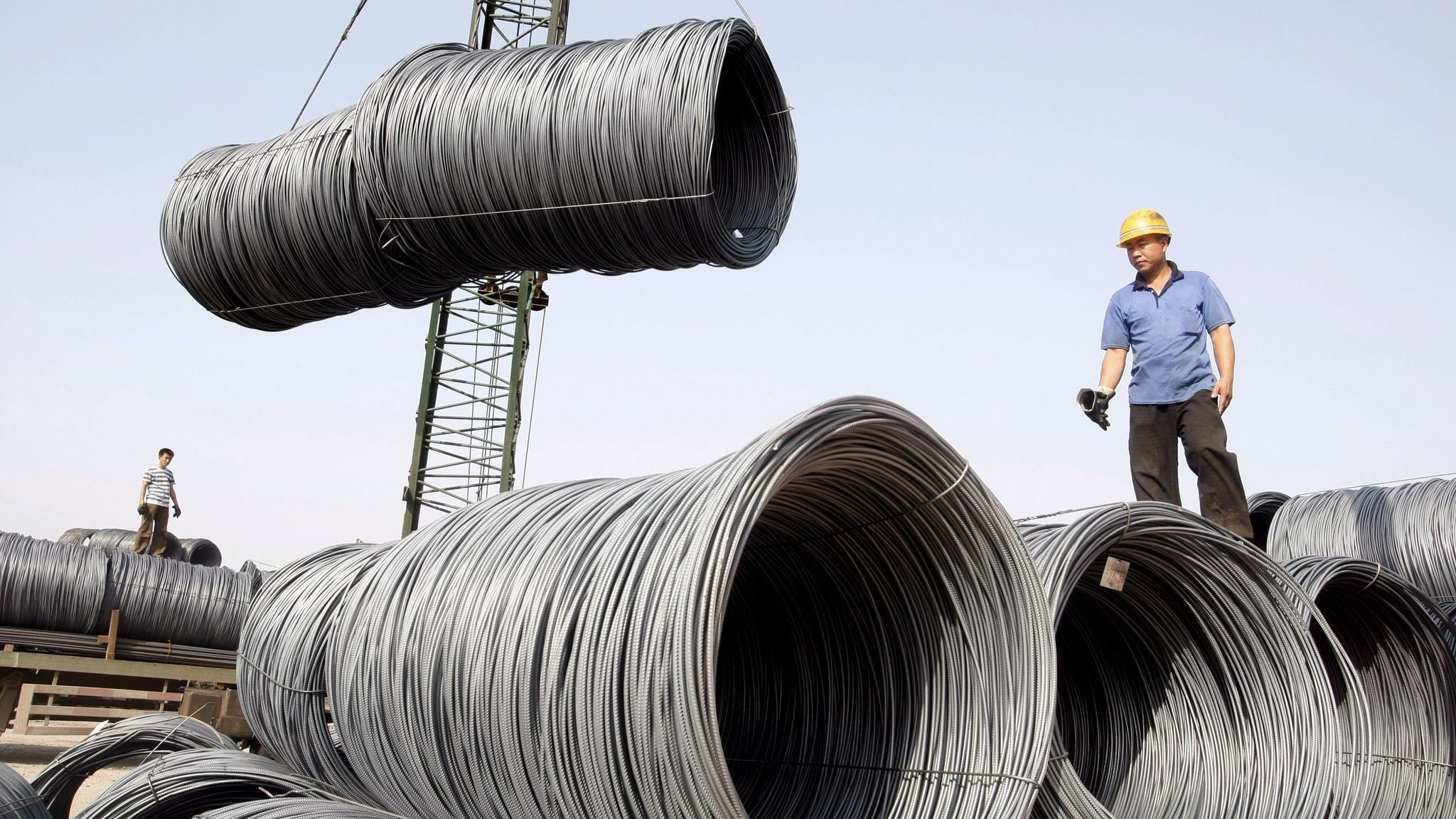 Workers transport steel cables at a steel yard in Beijing, China.