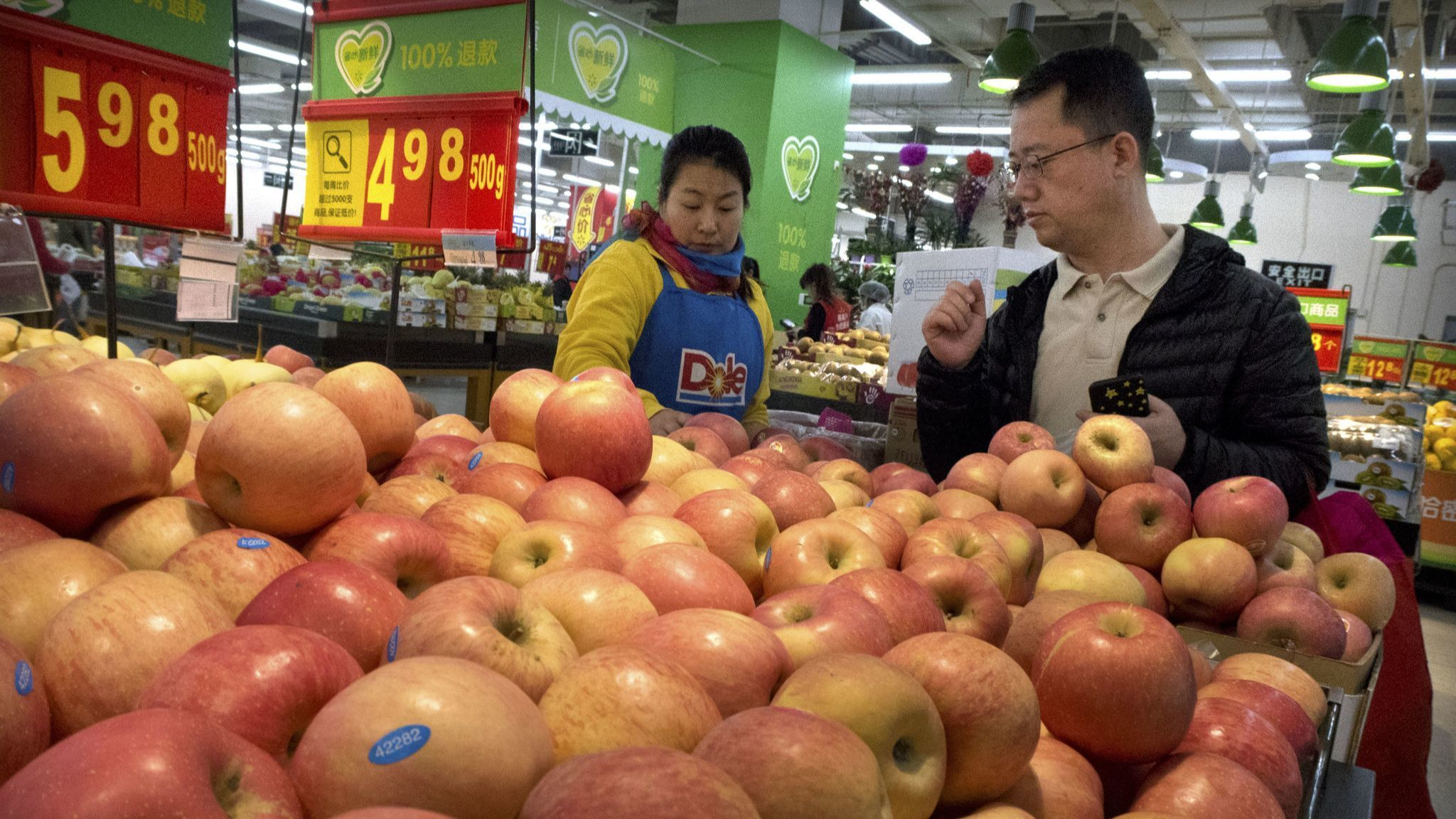 A customer shops for apples at a supermarket in Beijing.
