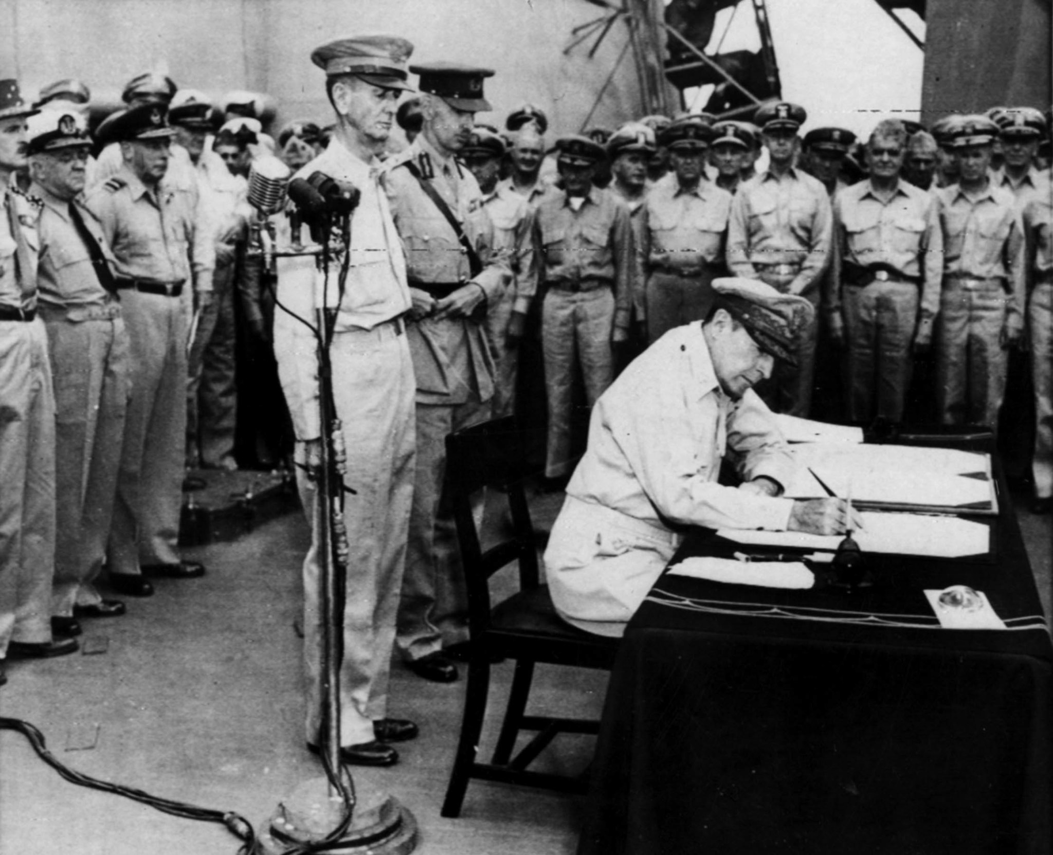 Sep. 2, 1945: Gen. Douglas MacArthur, seated, signs the Japanese surrender document aboard the USS M